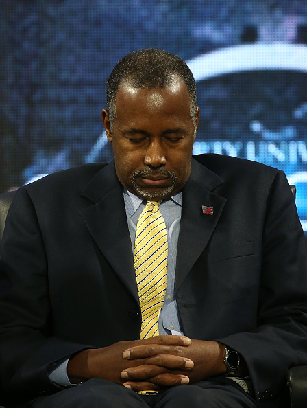 Dr. Ben Carson participates in a prayer during a rally at the University, on November 11, 2015 in Lynchburg, Virginia.