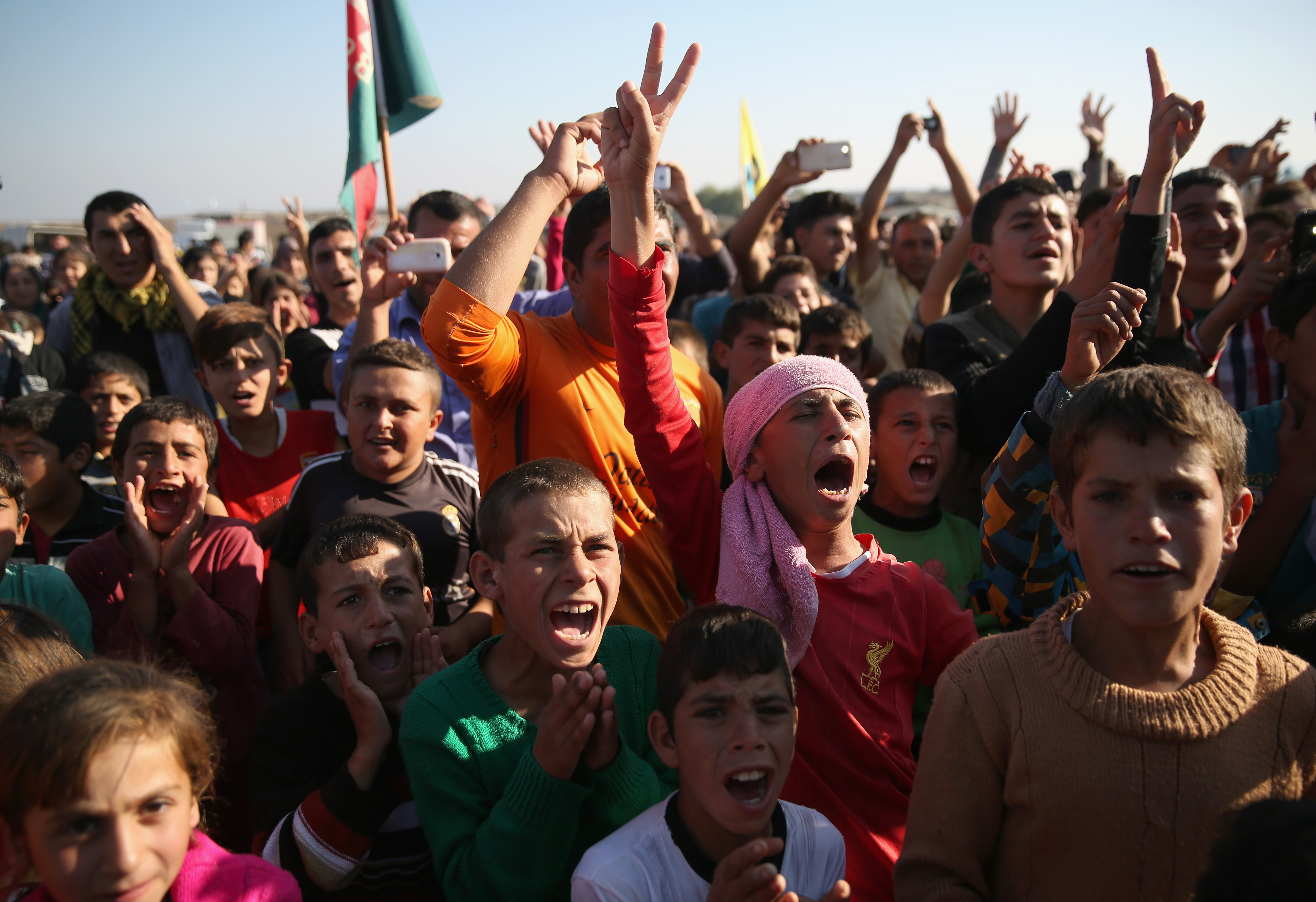 Yazidi refugees celebrate news of the liberation of their homeland of Sinjar from ISIS extremists, while at a refugee camp in Derek, Syria on Nov. 13, 2015.