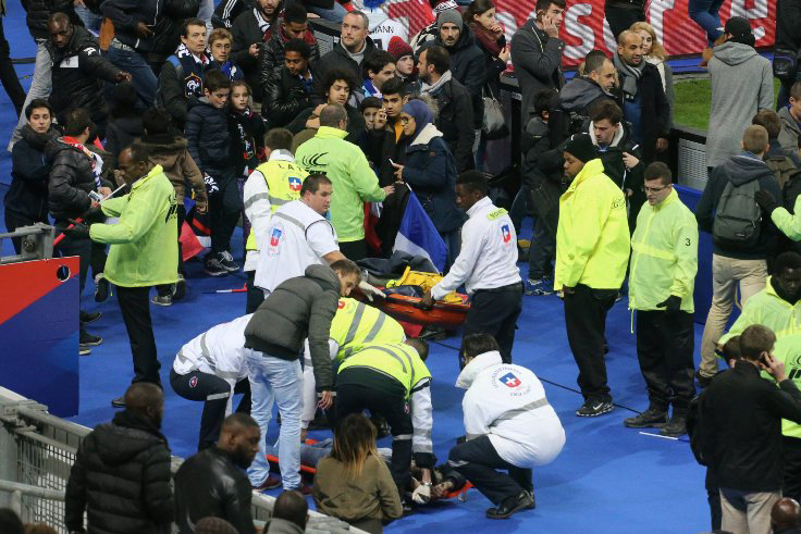 Crowds wait on the pitch during a soccer match at Stade de France on Nov. 13, 2015 in Paris, after the game was halted following an explosion.