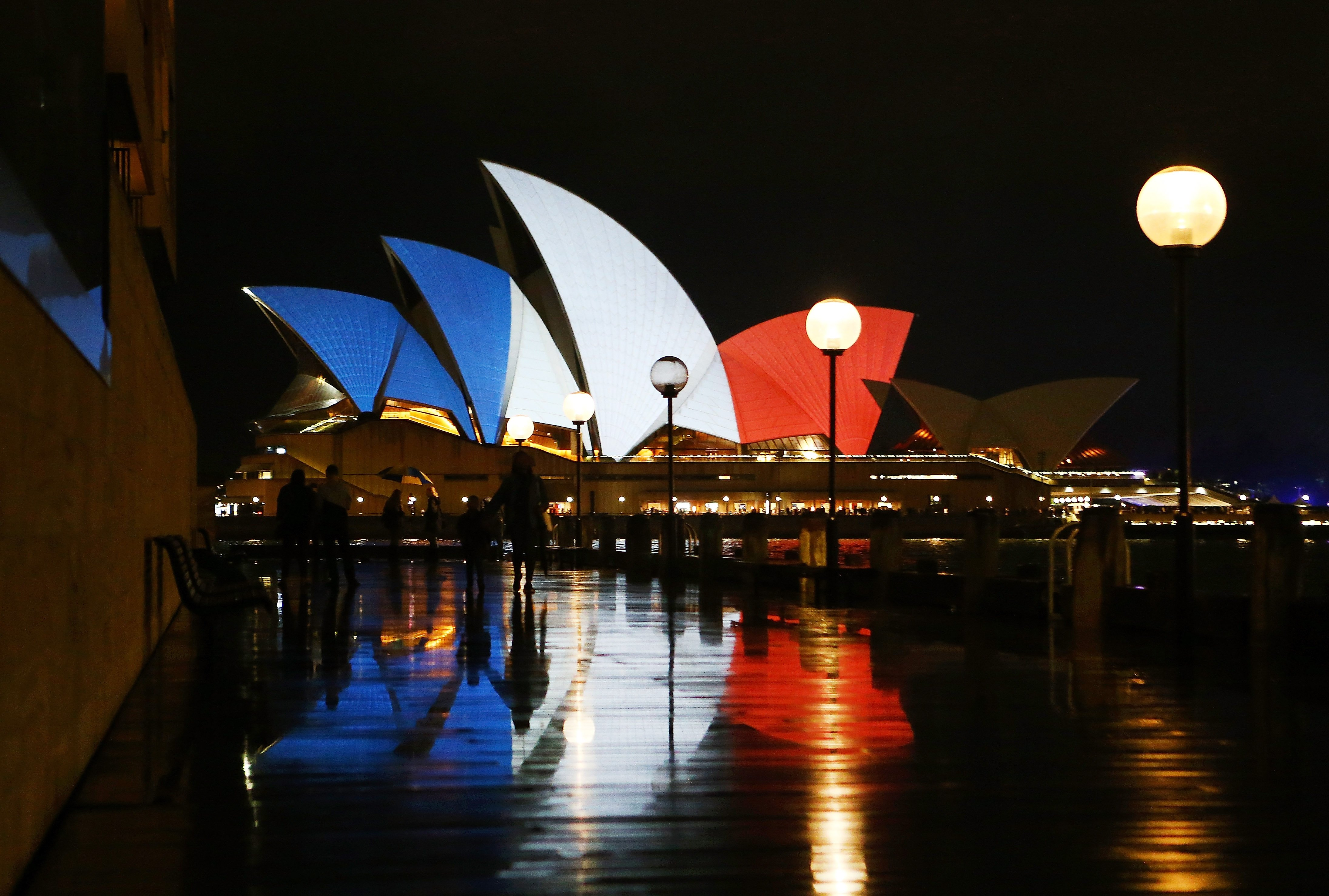 Pedestrians walk in front of the Sydney Opera House as its sails are illuminated in the colors of the French flag in Sydney, Australia on Nov. 14, 2015.