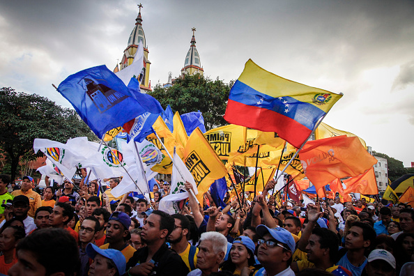 Attendees gather and wave flags during the kick off campaign for opposition candidates in the El Paraiso sector of Caracas, Venezuela, on Nov. 14, 2015