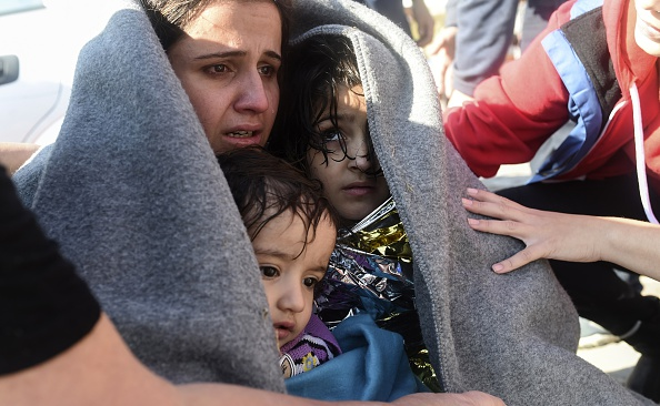 A mother hugs her children after disembarking as migrants and refugees arrive on the Greek island of Lesbos after crossing the Aegean Sea from Turkey on November 15, 2015