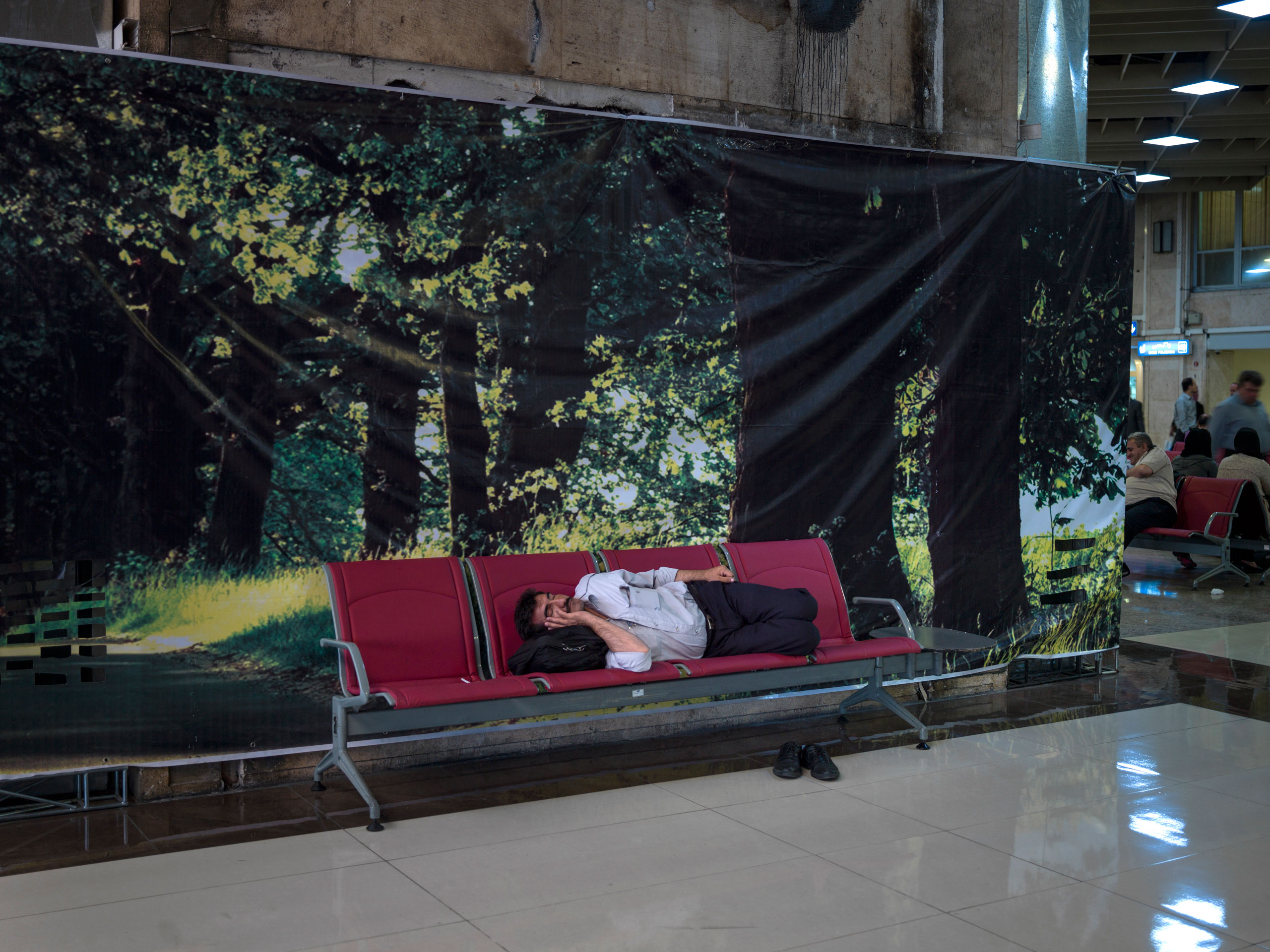 A man sleeps on a bench in Tehran's domestic Mehrabad airport. Following the nuclear agreement,  Iran hopes to upgrade its fleet of aging aircraft.