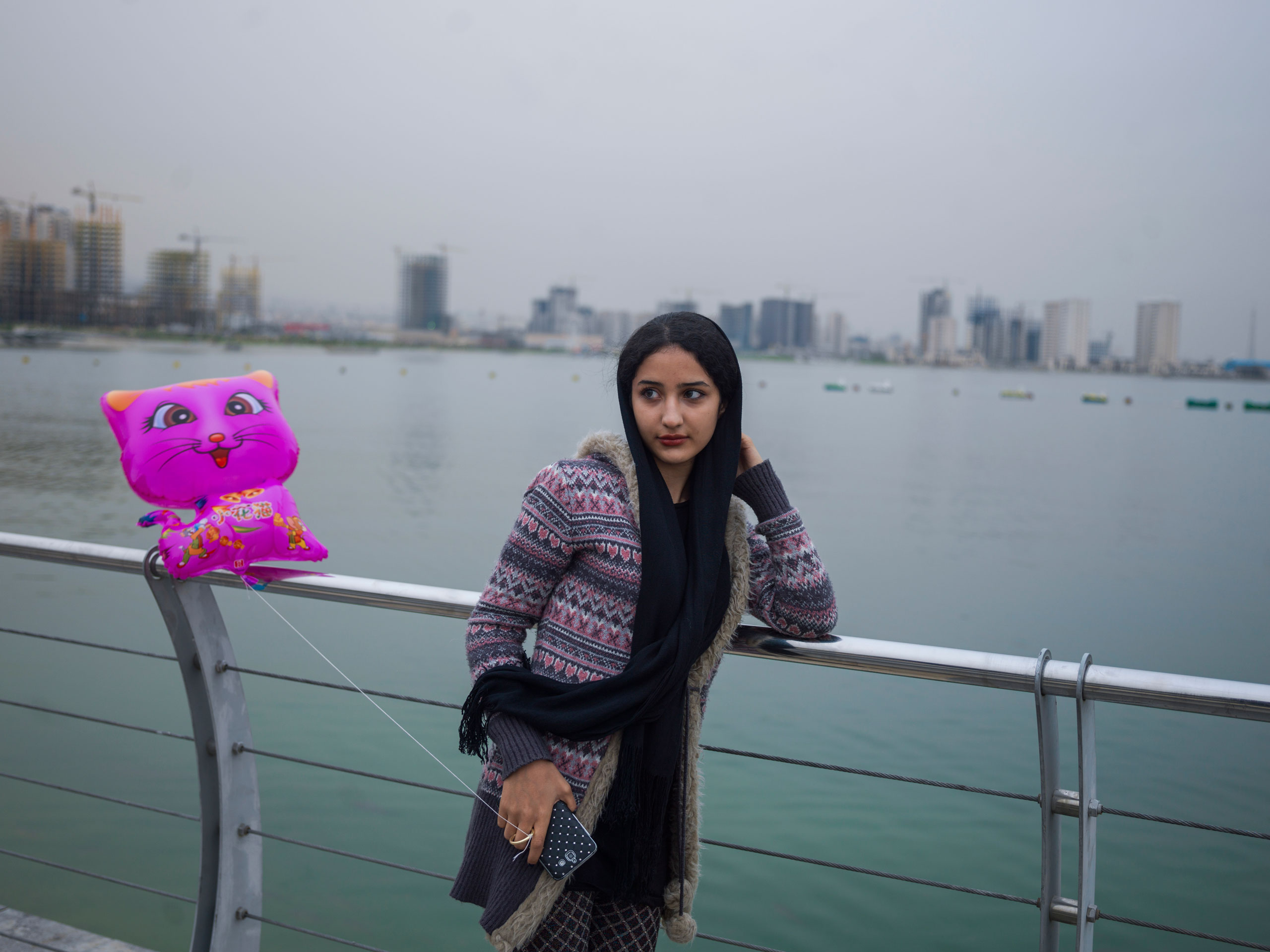 A young Iranian girl with her family visits an amusement park beside the new artificial lake dubbed Persian Gulf of Martyrs on Tehran's west side.