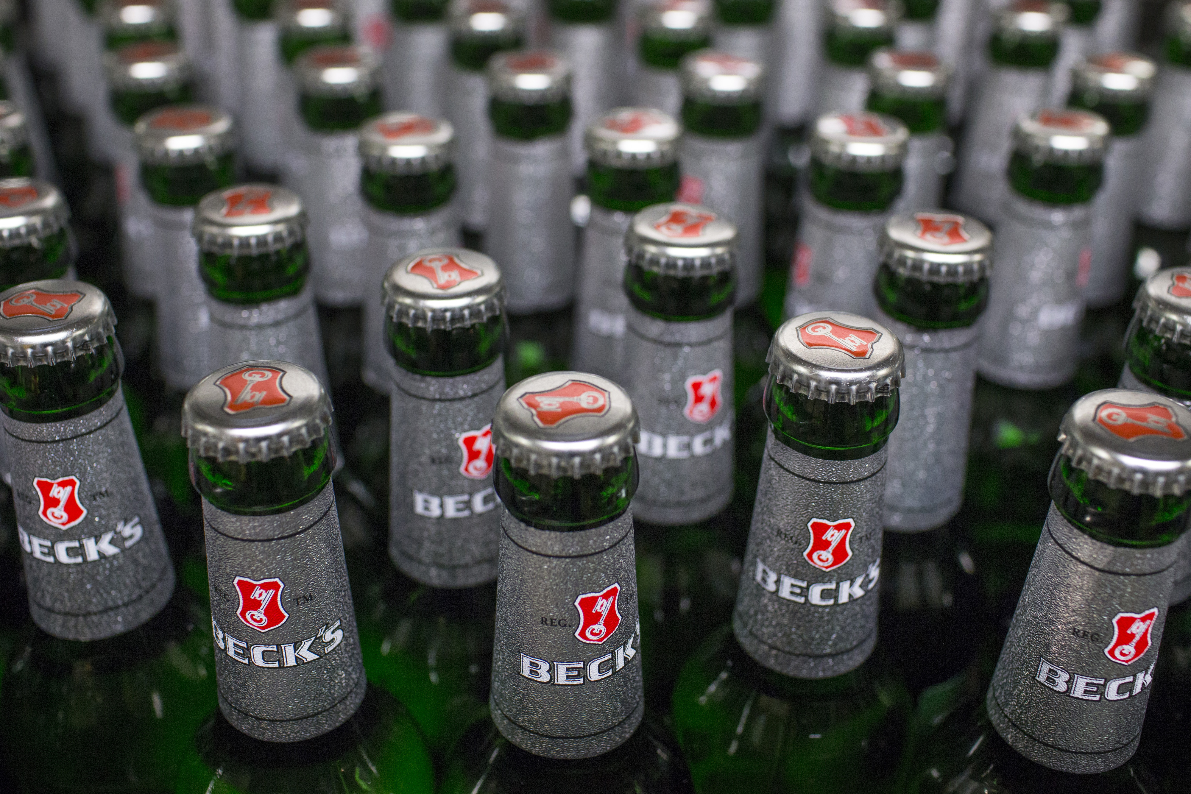 Bottles of Beck's lager beer move along the production line at the Beck's brewery, operated by Anheuser-Busch InBev NV, in Bremen, Germany on Nov. 4, 2015.