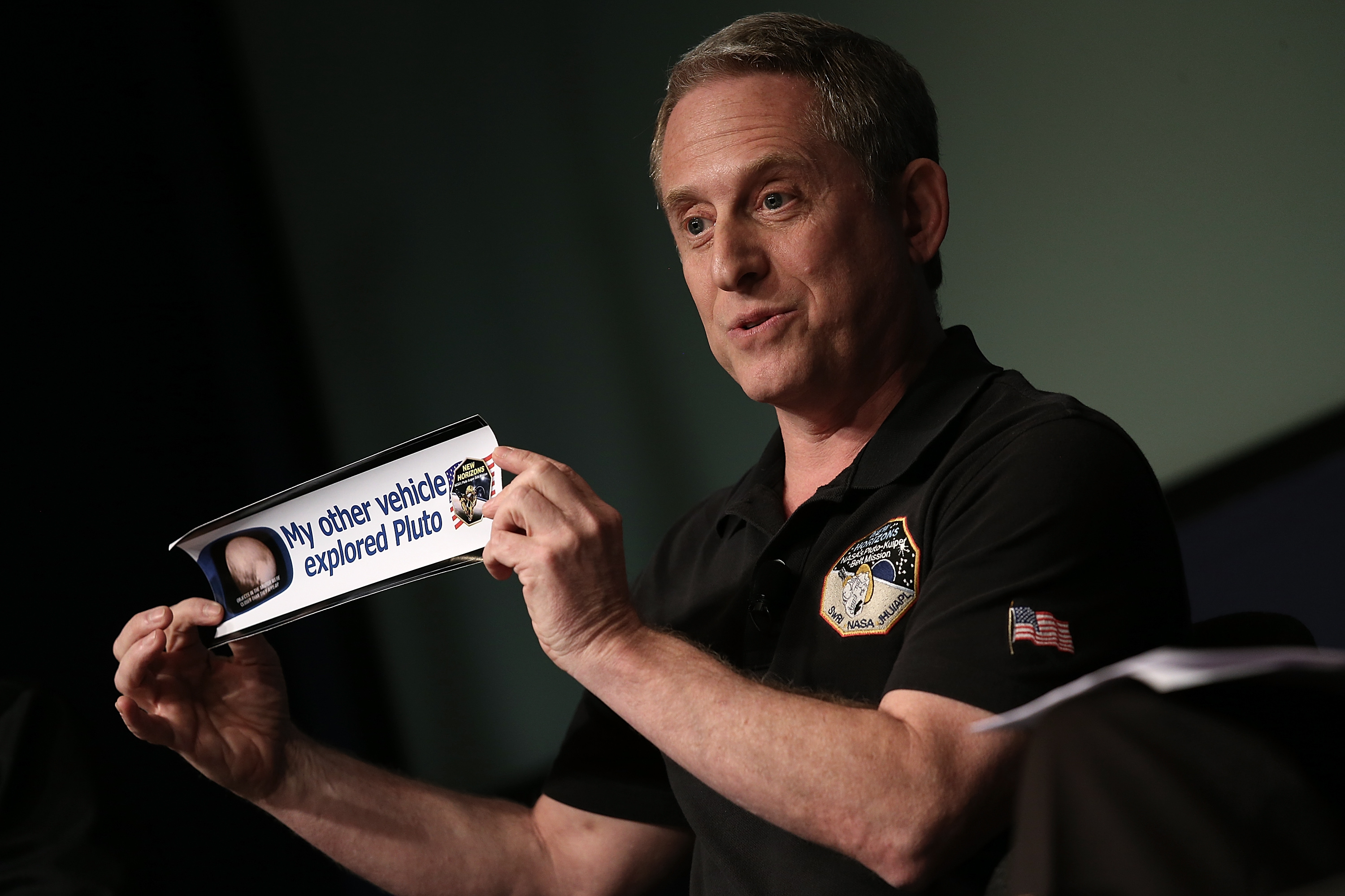 Alan Stern, principal investigator of NASA's New Horizons mission team, holds up a bumper sticker while delivering remarks during a press briefing at NASA headquarters in Washington, DC on July 24, 2015.