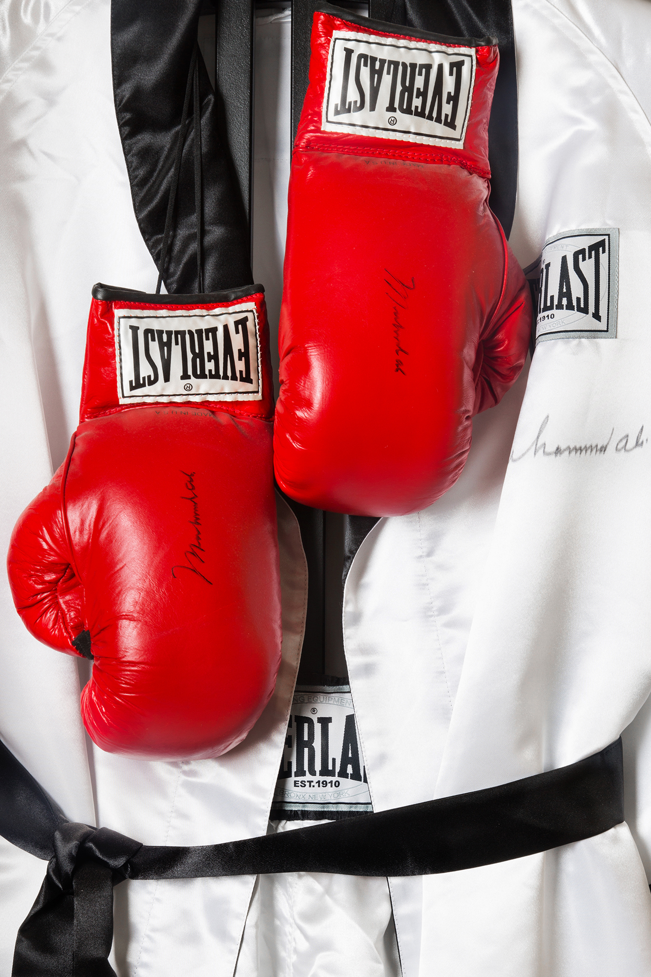 """Muhammad Ali Gloves and Robe:  These autographed boxing gloves and robe were worn by Muhammad Ali, who has appeared on the cover of Sports Illustrated 39 times since 1963—the most prolific cover athlete other than Michael Jordan. Sports Illustrated renamed its Legacy Award the Muhammad Ali Legacy Award in September to honor the boxer.  To have an award named in my honor by Sports Illustrated is something I could have never expected as a young man back in 1963 when I posed for that first cover. I am truly touched,"""" Ali said"""