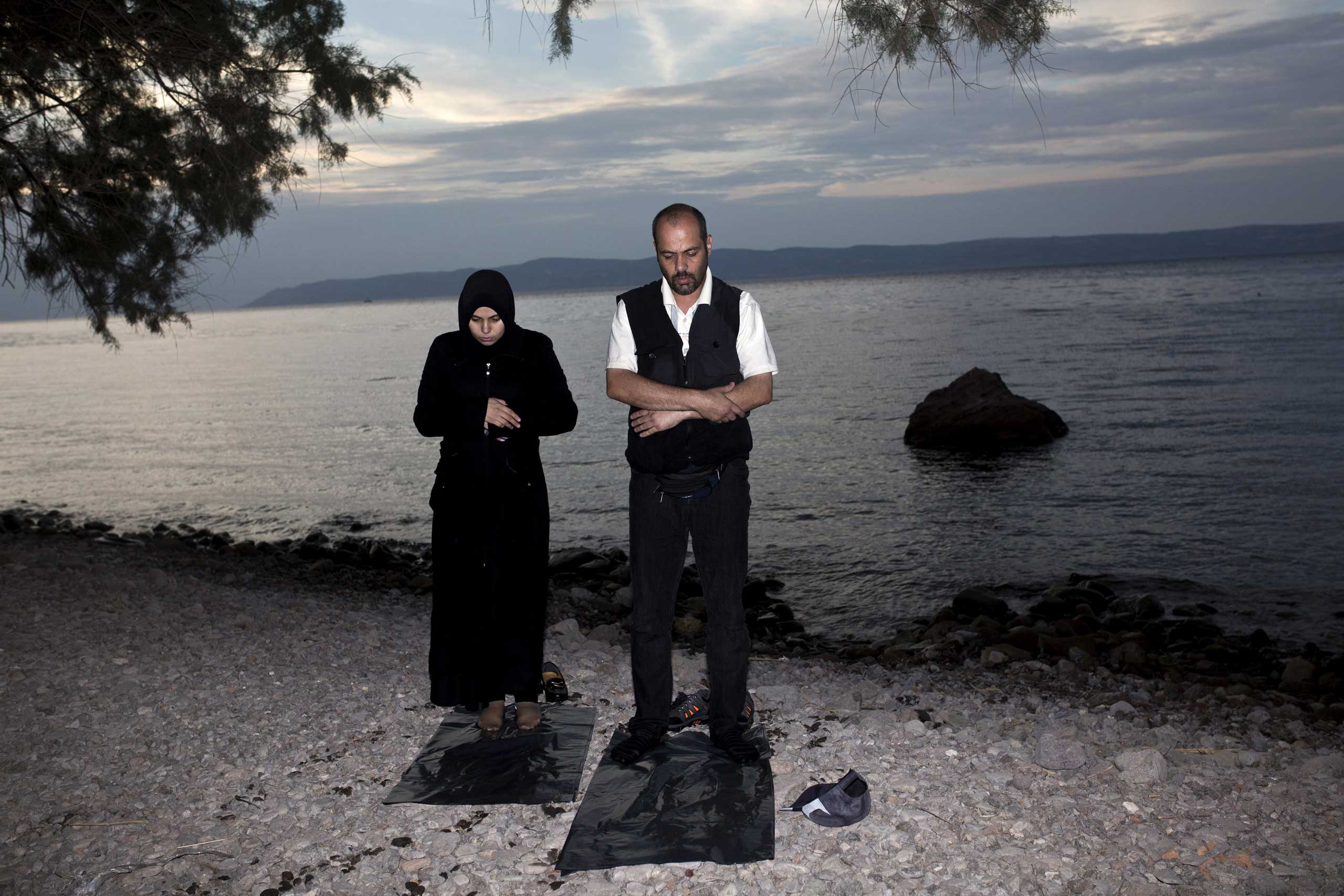 Migrants pray after arriving on the shores of the Greek island of Lesbos, Sept. 9, 2015.