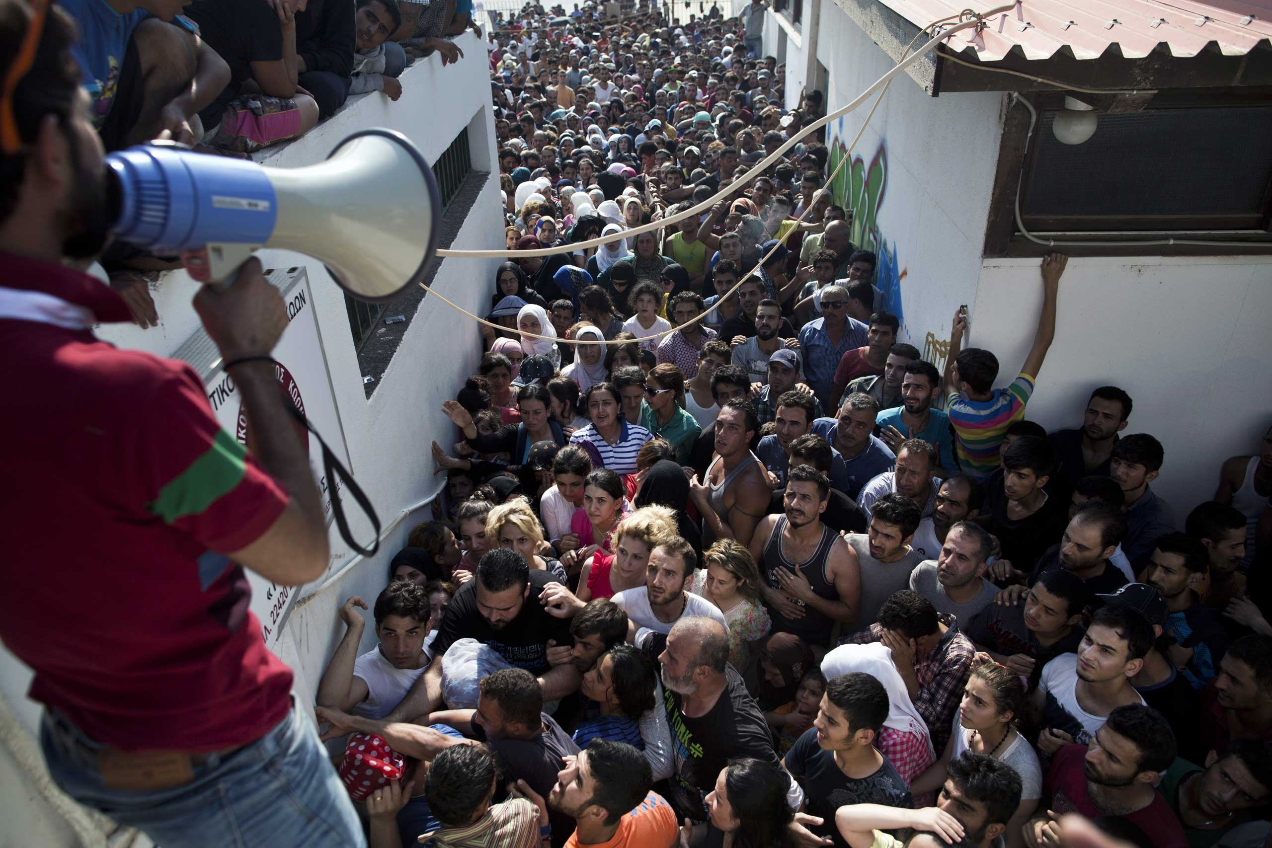 Migrants wait for a registration procedure at the stadium on the Greek island of Kos, Aug. 11, 2015.