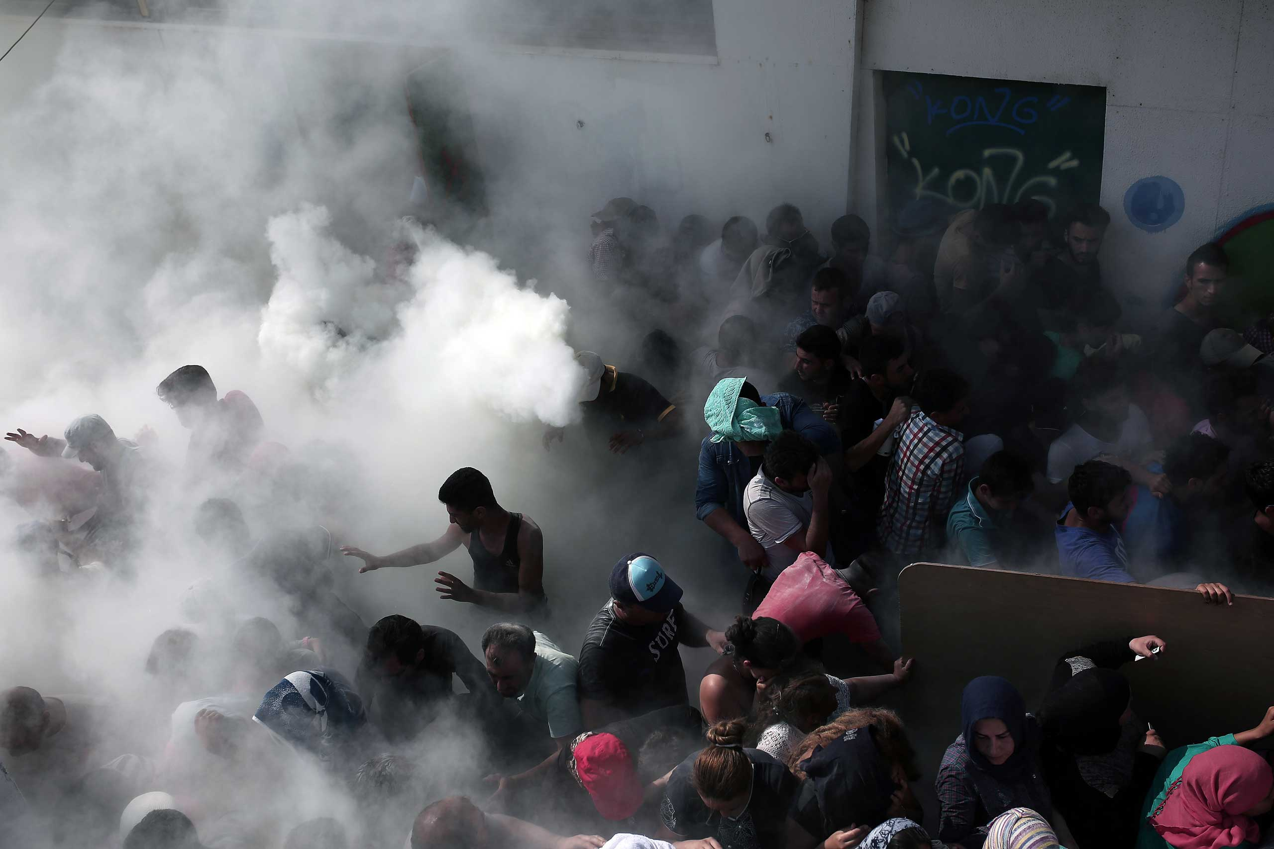 Policemen try to disperse hundreds of migrants by spraying them with fire extinguishers during a gathering for a registration procedure at the stadium on the Greek island of Kos, Aug. 11, 2015.