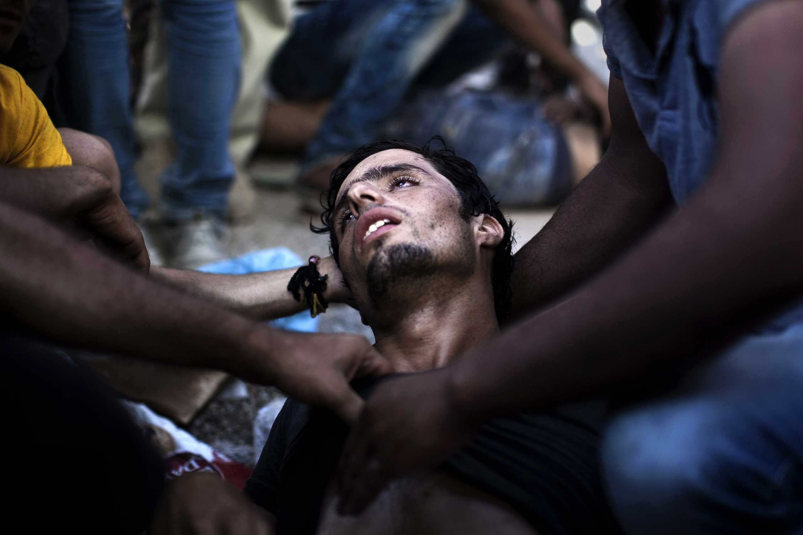 A migrant collapses as police officers try to disperse migrants waiting to be registered by the police at the Lesbos Port, Sept. 5, 2015.