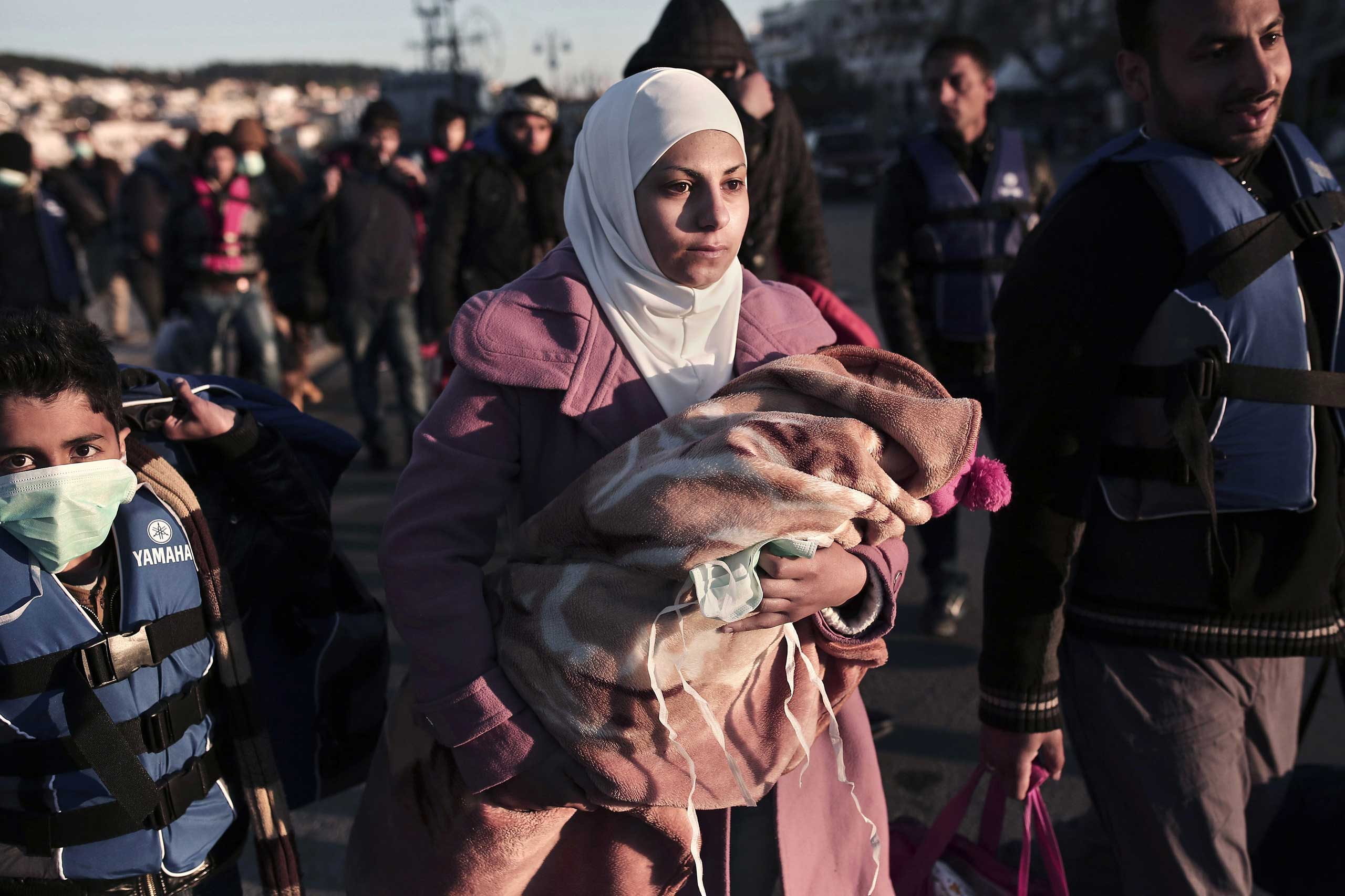 A migrant from Syria holds her child upon arrival in Greece at the port of Lesbos island, April 16, 2015.