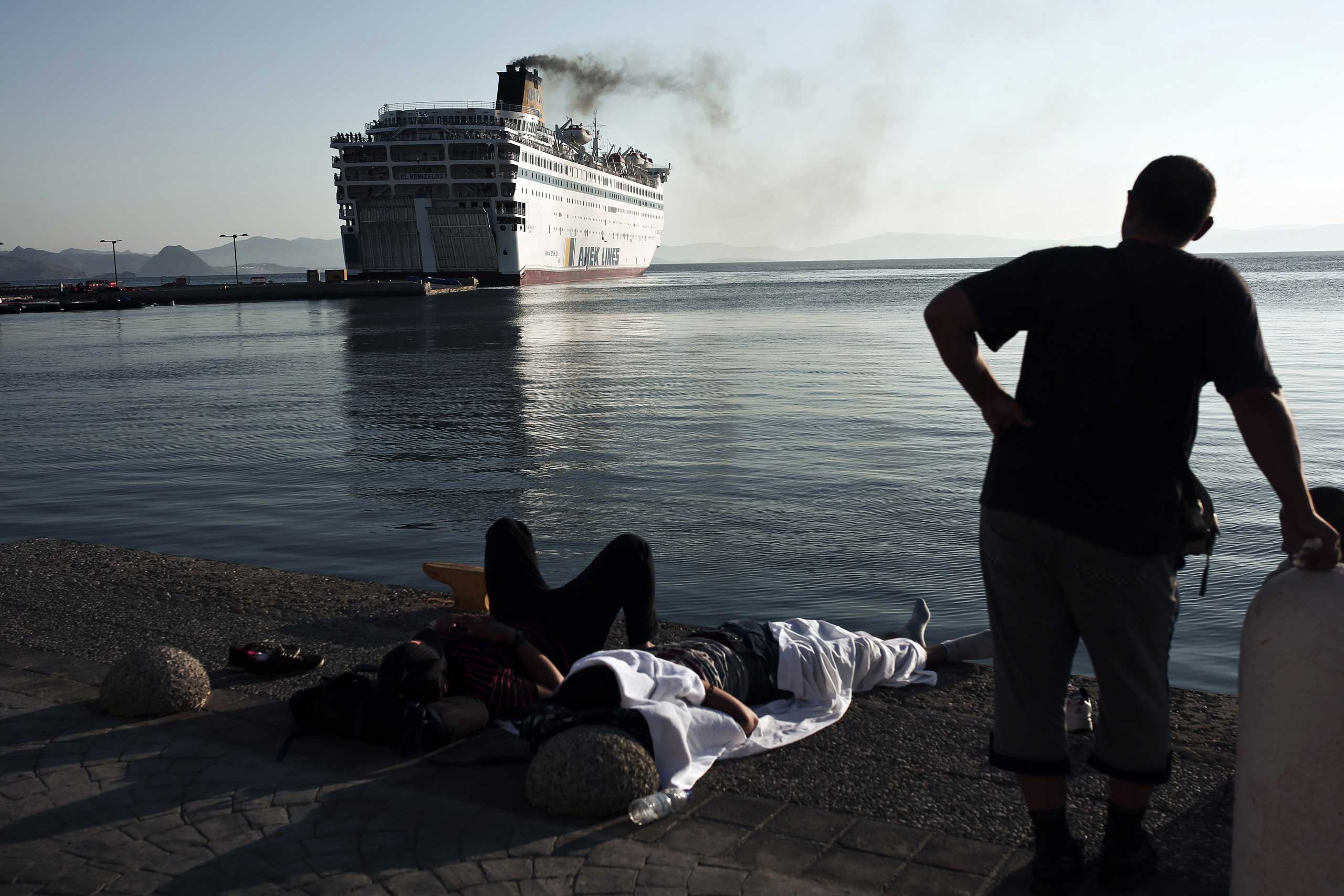 A migrant looks at the passenger ship  Eleftherios Venizelos  leaving the port of the Greek island of Kos, Aug. 19, 2015.