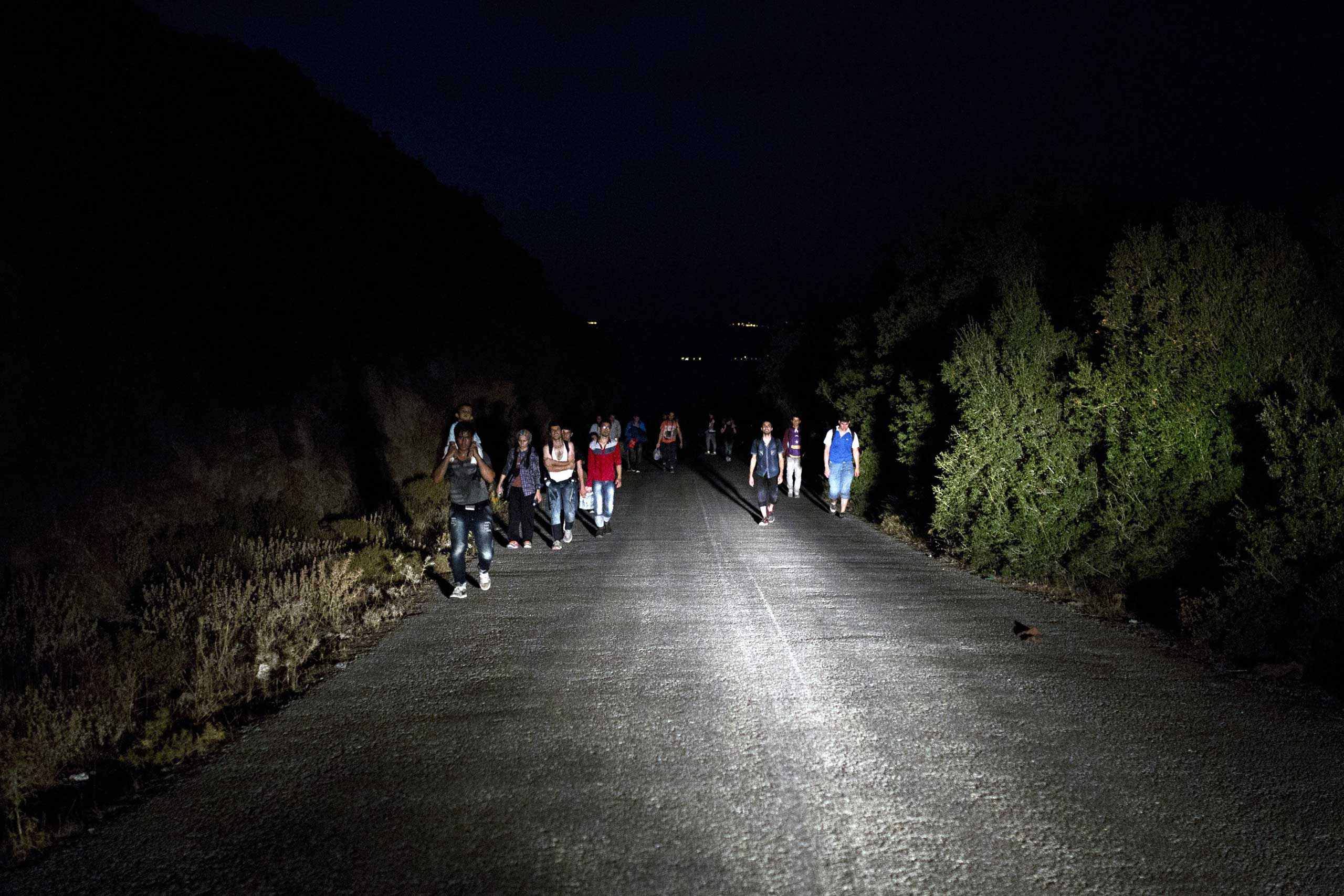 Migrants walk on the street towards Mytilene on the Greek island of Lesbos, Sept. 8, 2015.