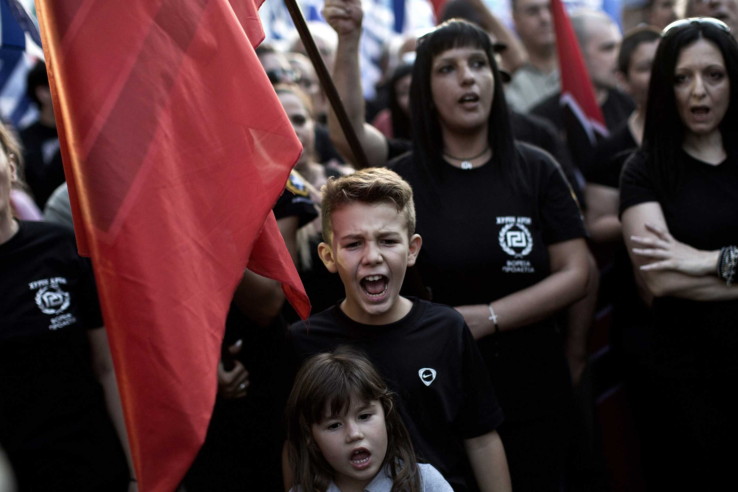 Supporters of the Greek Golden Dawn extreme right party shout slogans during a pre-election rally in Athens, Sept. 16, 2015.
