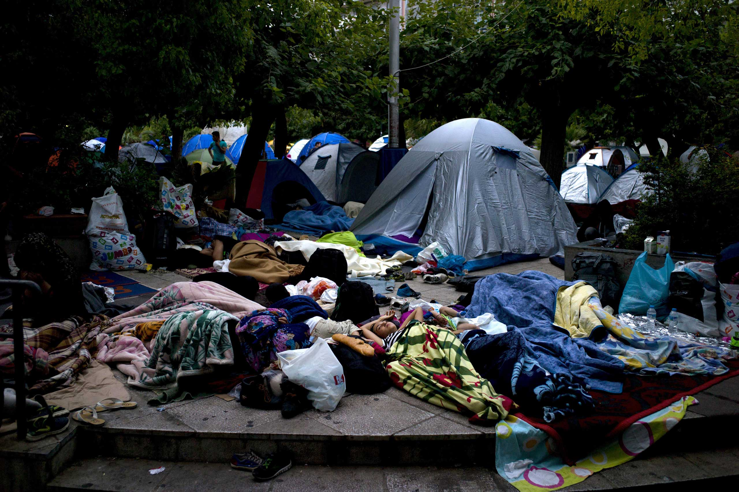 Migrants and refugees sleep on the ground in Victoria Square, where hundreds of migrants and refugees found temporary refuge, in central Athens, Sept. 26, 2015.