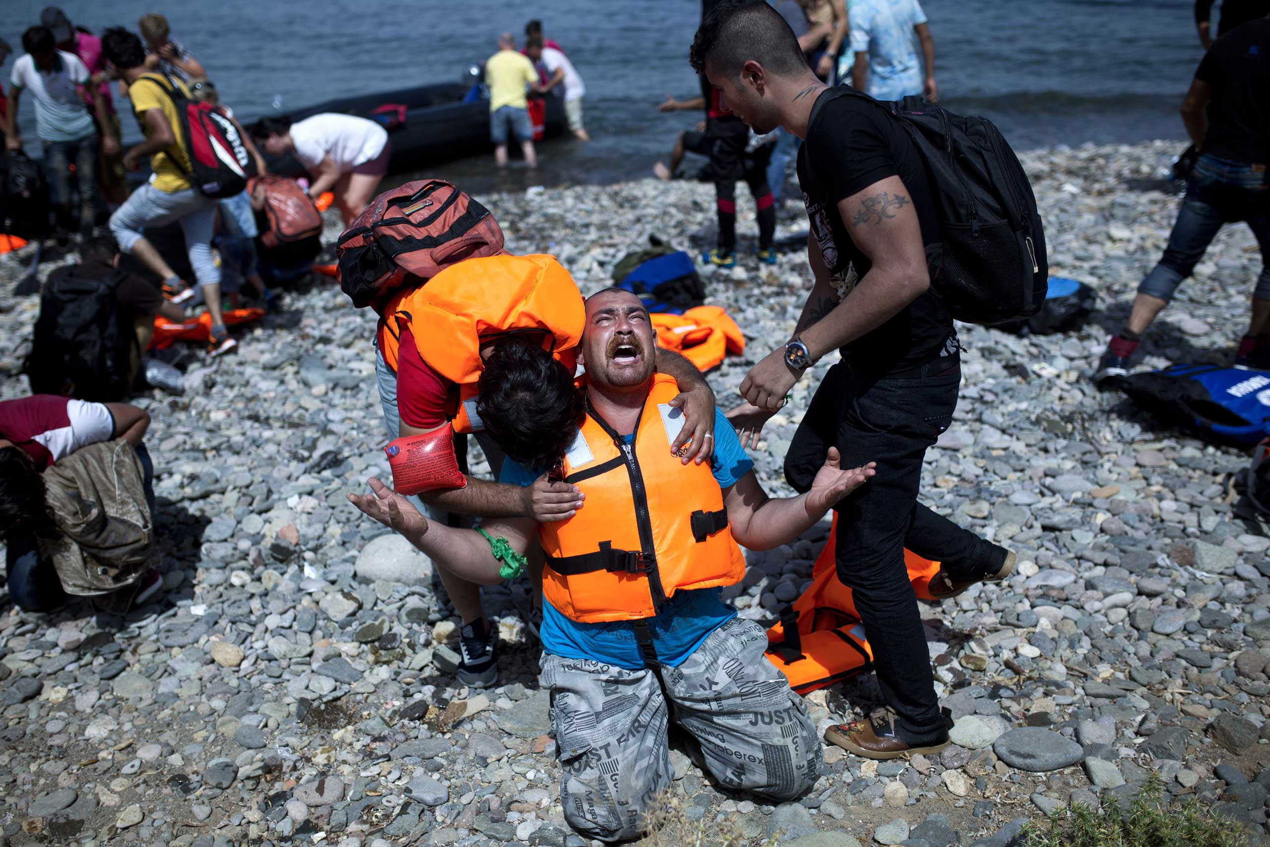 A refugee from Syria prays after arriving on the shores of the Greek island of Lesbos aboard an inflatable dinghy across the Aegean Sea from from Turkey, Sept. 7, 2015.