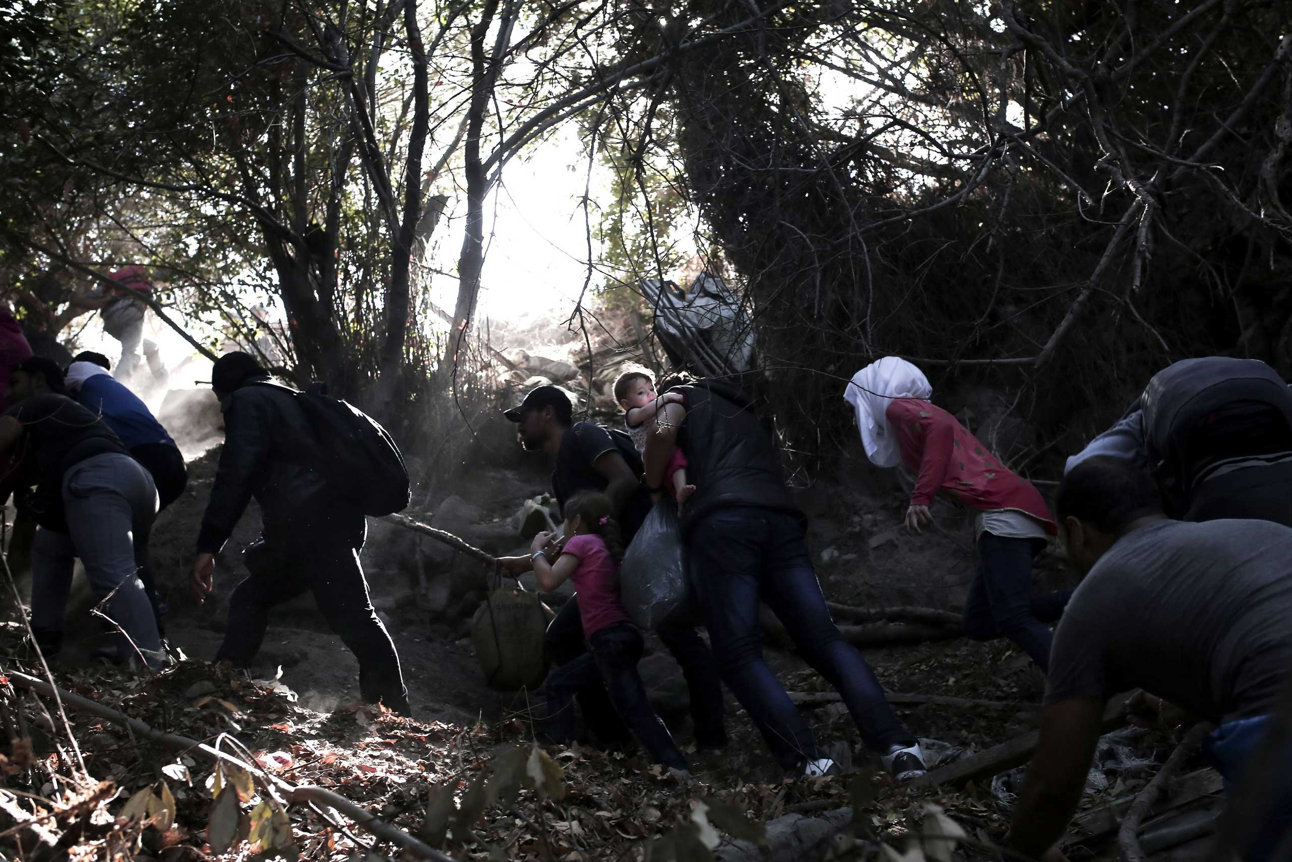 Syrian refugees try to climb a slope after arriving from Turkey on the shores of the Greek island Lesbos, Sept. 11, 2015.