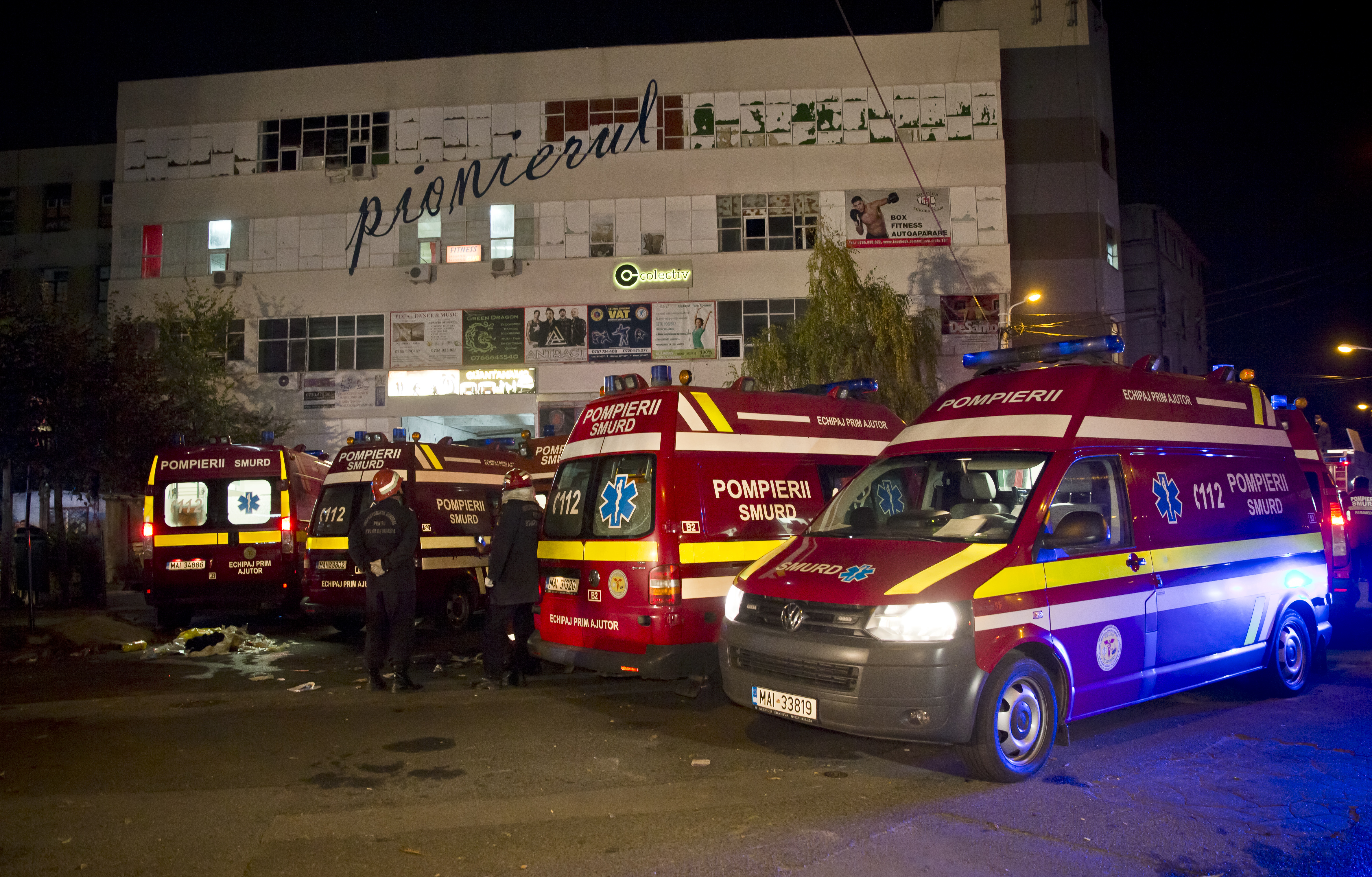 Ambulances are parked outside the site of a fire that occurred in a club, housed by the building in the background, in Bucharest.