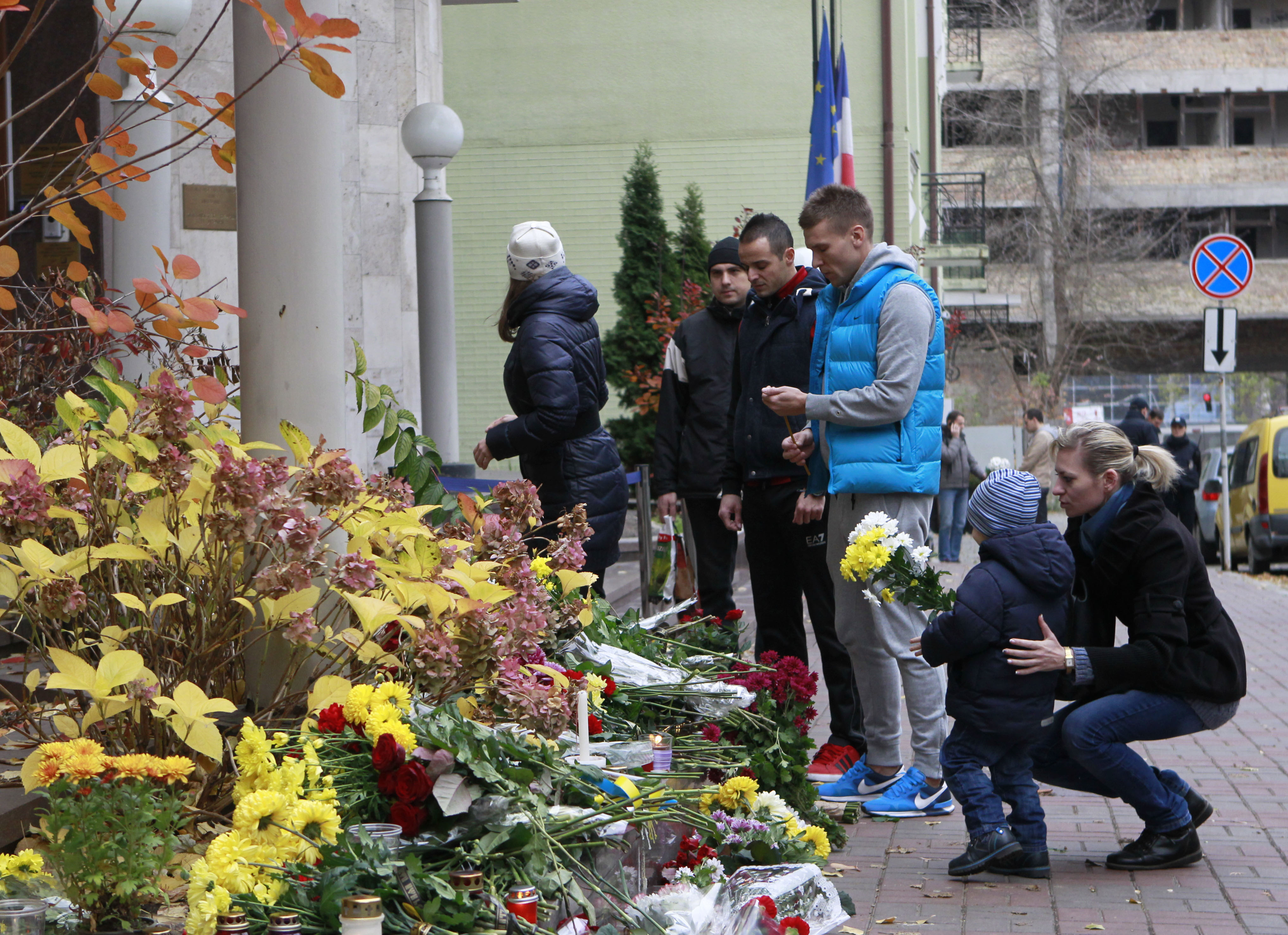 People lay flowers in front of the French Embassy in Kiev, Ukraine on Nov. 14, 2015.