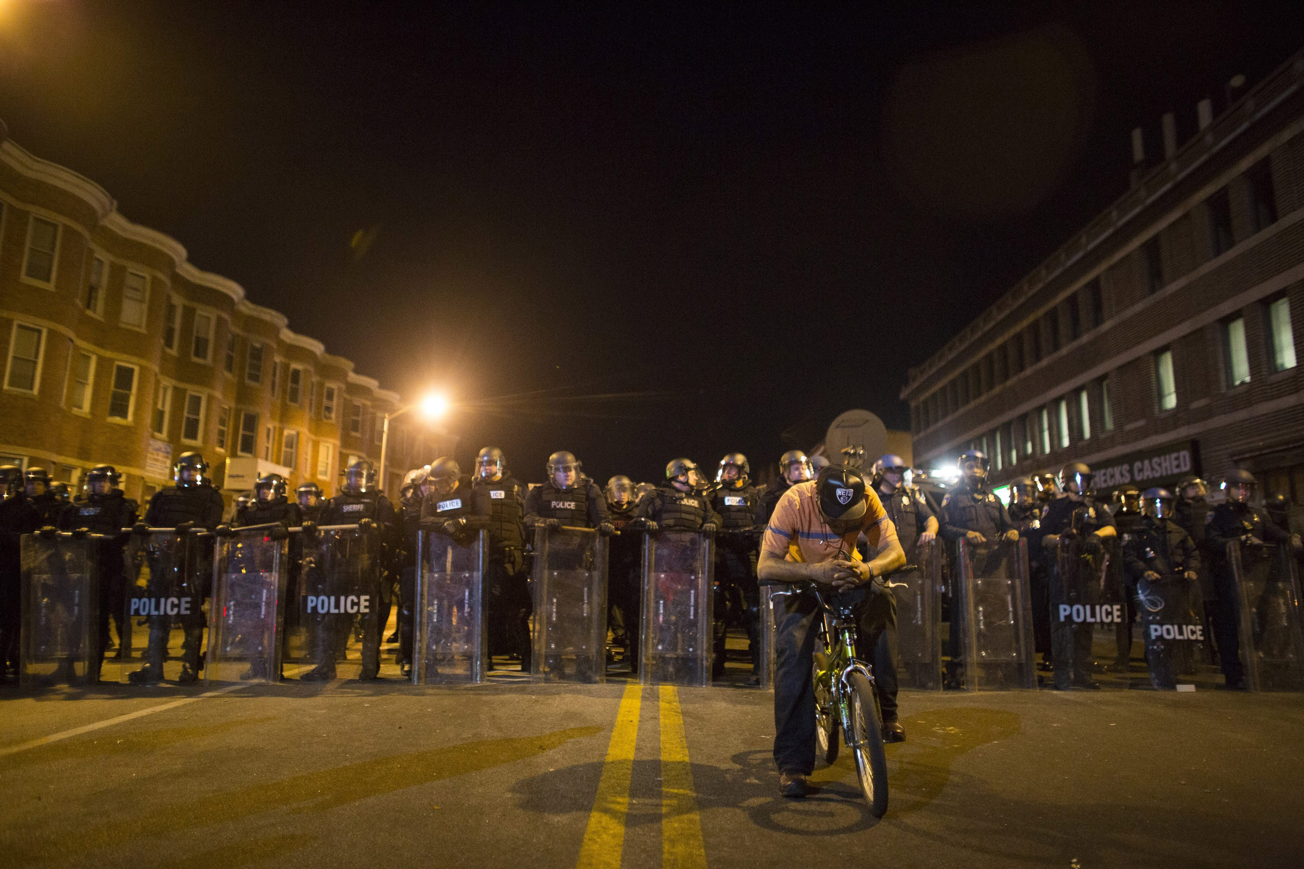 A protester on his bike is seen in front of a line of policemen in riot gear during a 10 p.m. curfew in Baltimore on Apr. 28, 2015.