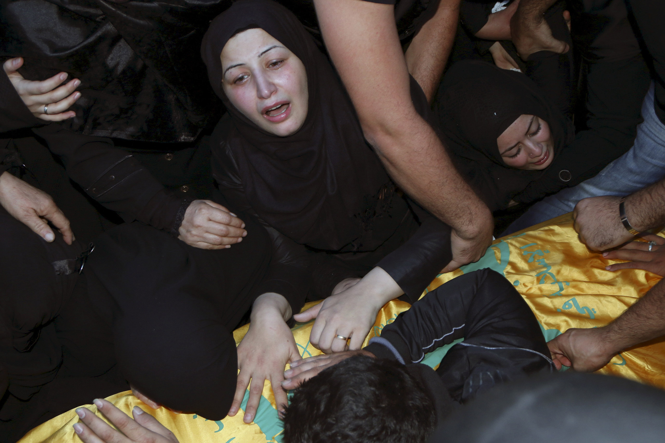 Relatives mourn over the coffin of Hezbollah member Adel Akram Termos, who was killed in the two explosions that occurred on Thursday in Beirut's southern suburbs, during his funeral in Tallousa, southern Lebanon, on Nov. 13, 2015.
