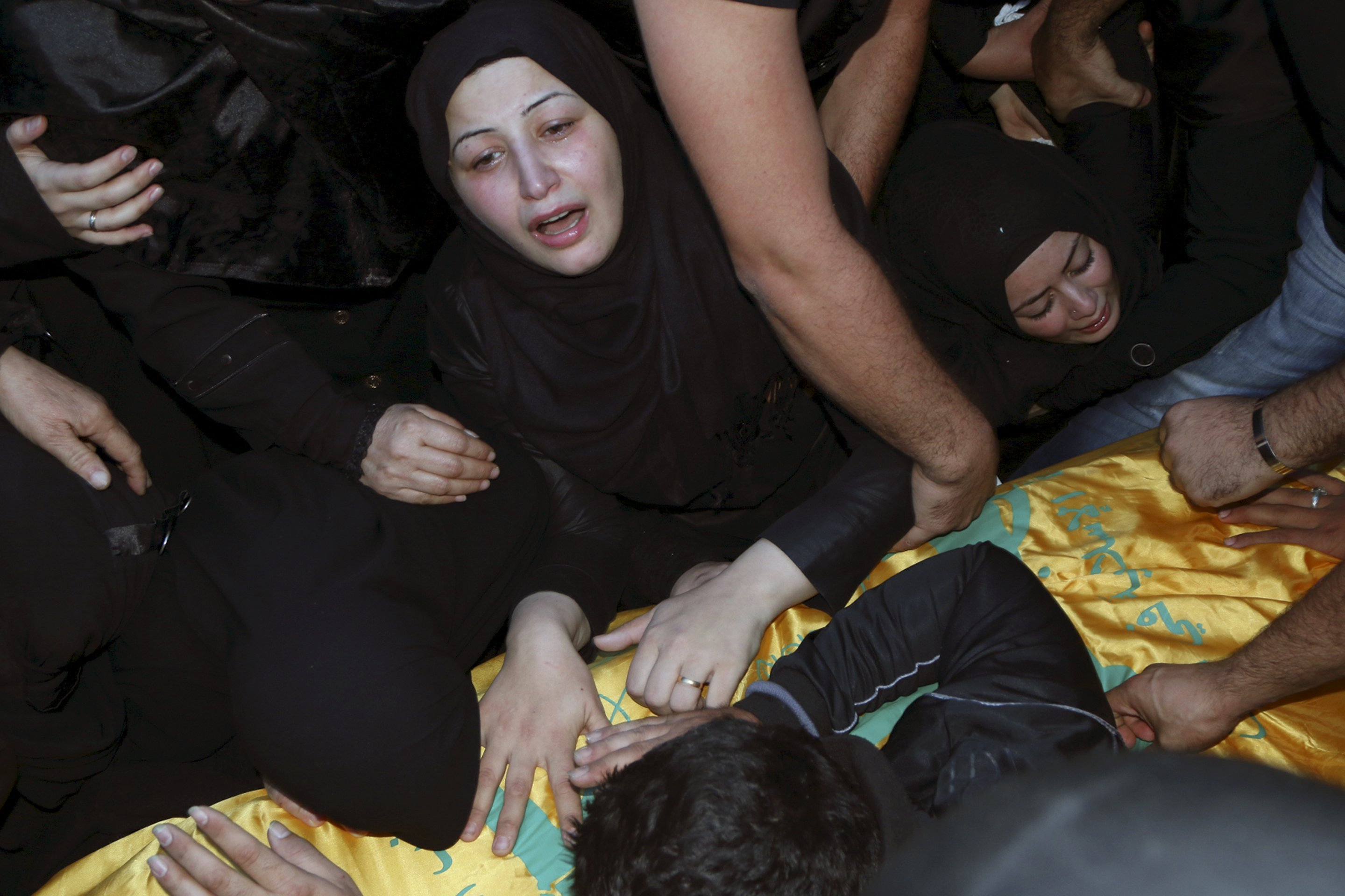 Relatives mourn over the coffin of Hezbollah member, Adel Akram Termos, who was killed in the two explosions that occurred on Thursday in Beirut's southern suburbs, during his funeral in Tallousa village, southern Lebanon on Nov. 13, 2015.