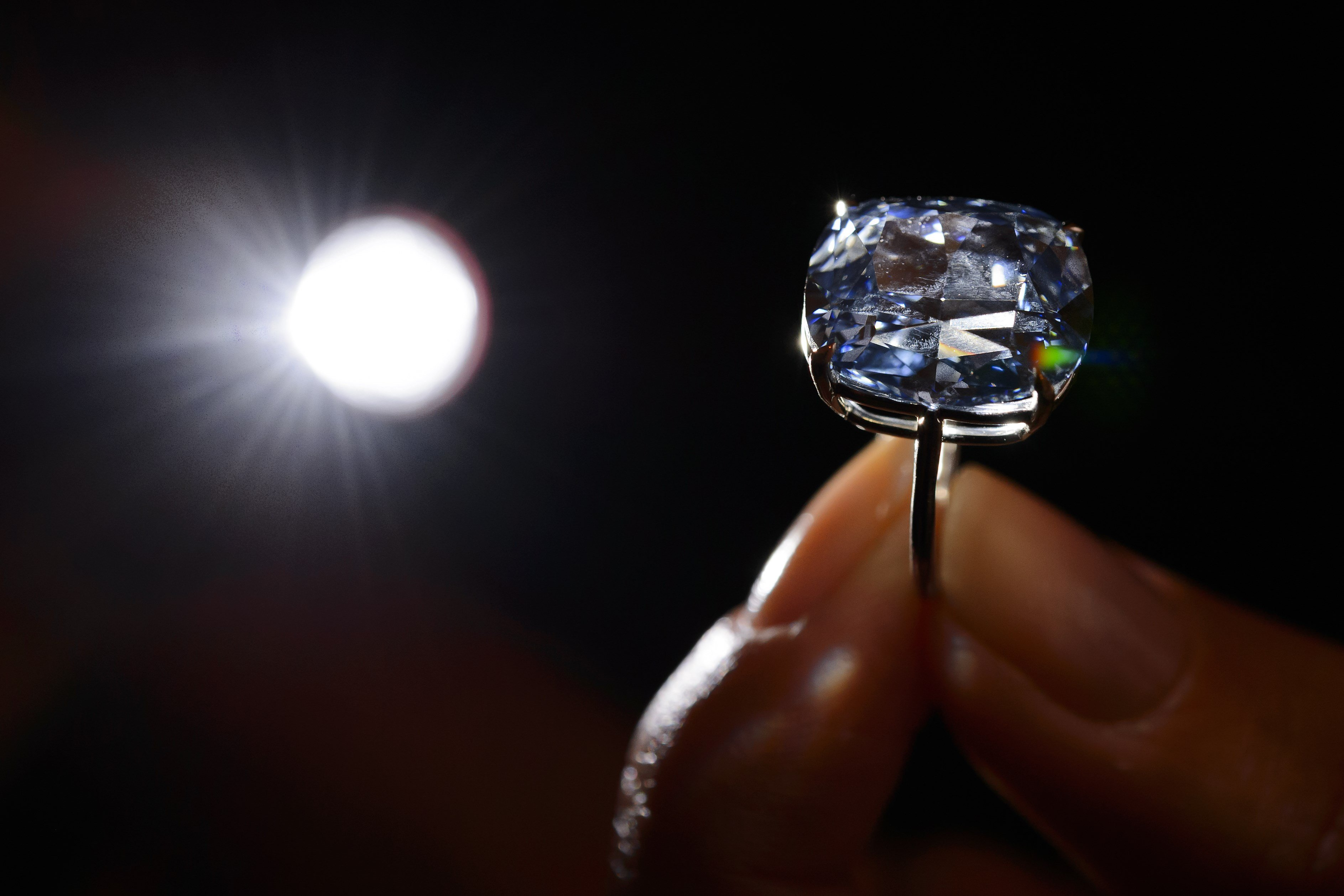 A model holds the 12.03-carat Blue Moon diamond during a press preview by auction house Sotheby's in Geneva on Nov. 4, 2015.