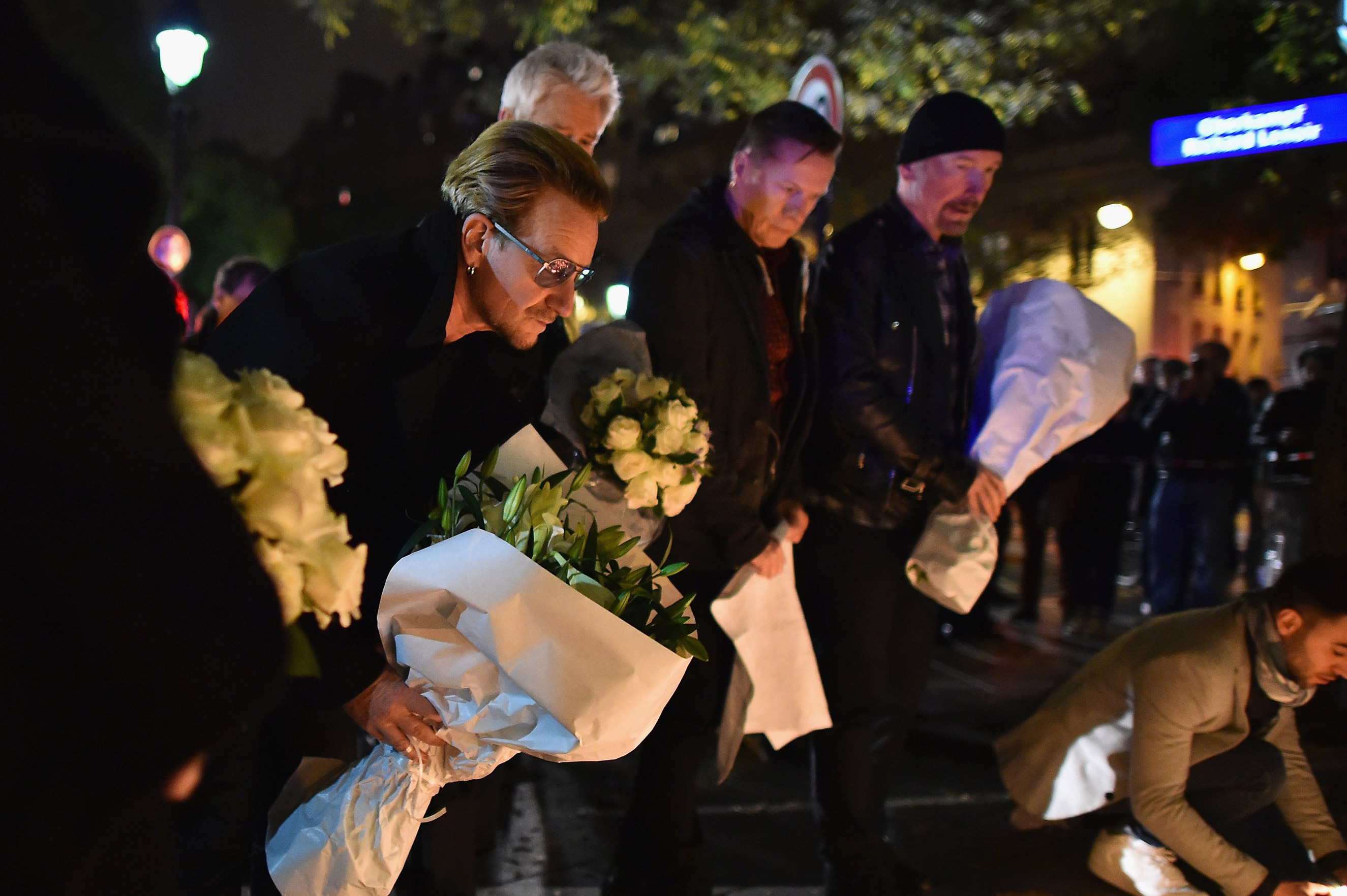 Bono and band members from the band U2 place flowers on the pavement near the scene of yesterday's Bataclan Theatre terrorist attack on Nov. 14, 2015 in Paris.