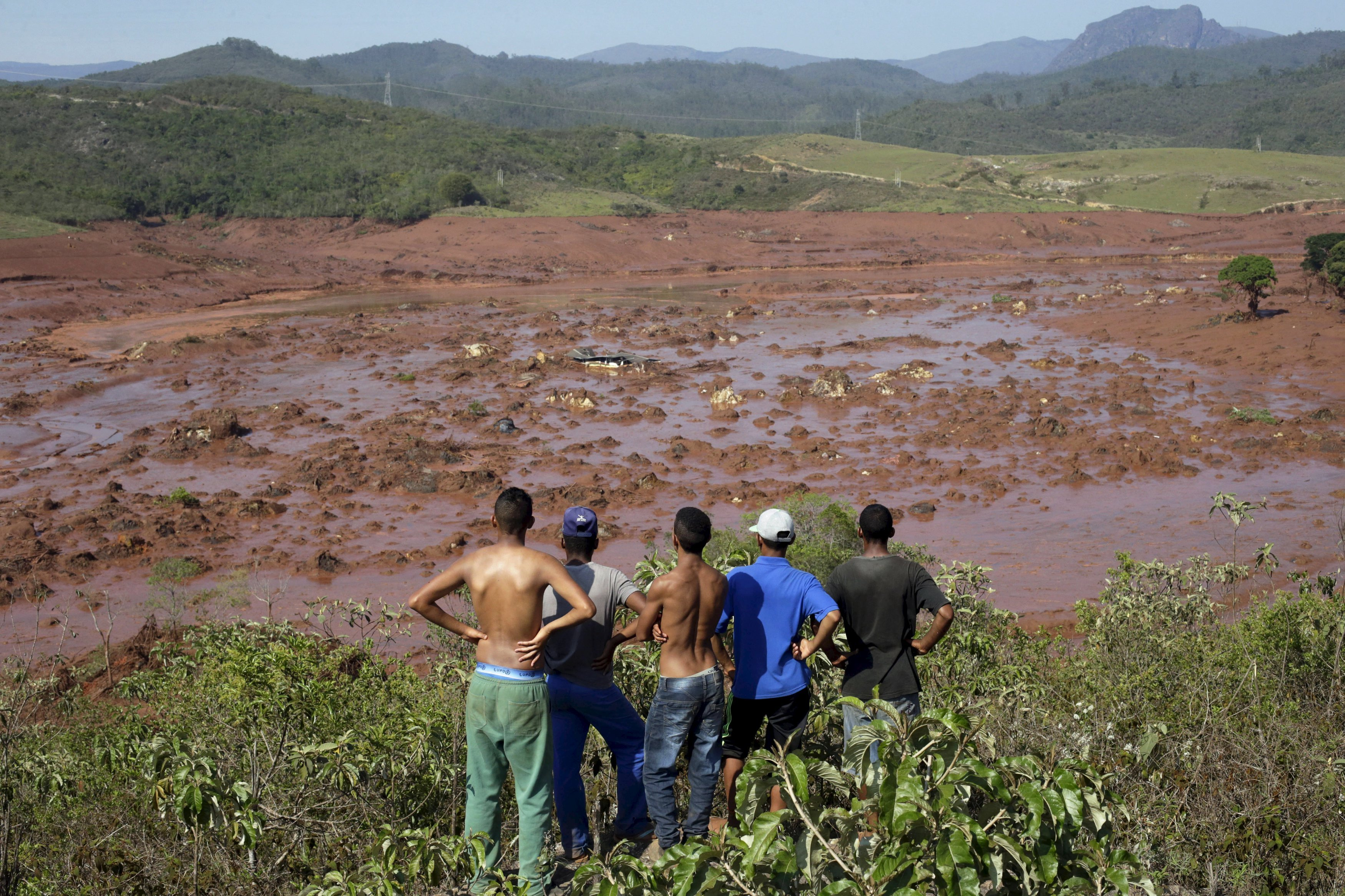 Residents observe the Bento Rodrigues district covered with mud after a dam owned by Vale SA and BHP Billiton Ltd burst in Mariana, Brazil, on Nov. 6, 2015.