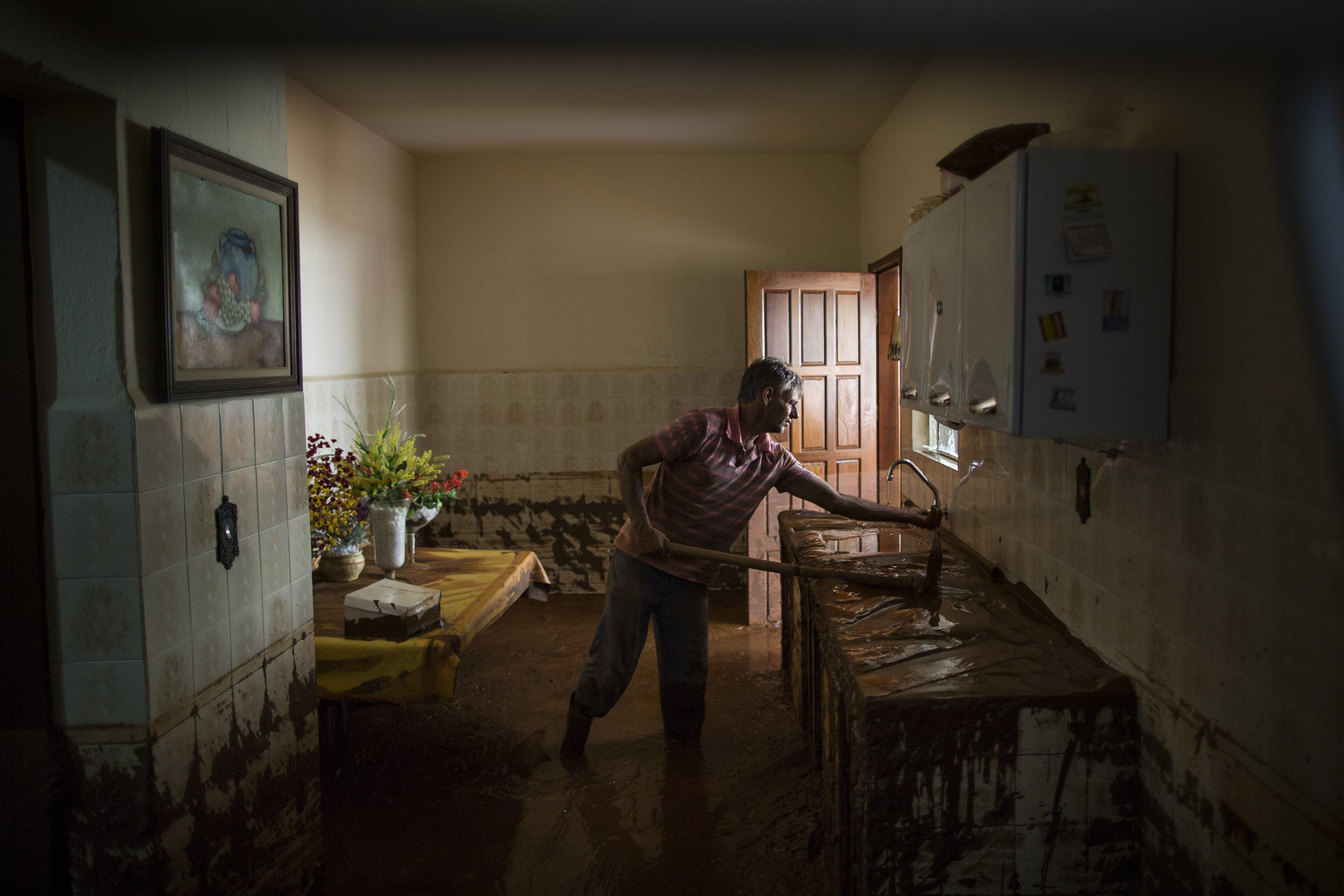 Antonio Carlos Carneiro removes mud from his damaged home in Barra Longa after a dam burst in Minas Gerais state, Brazil on Nov. 7, 2015.