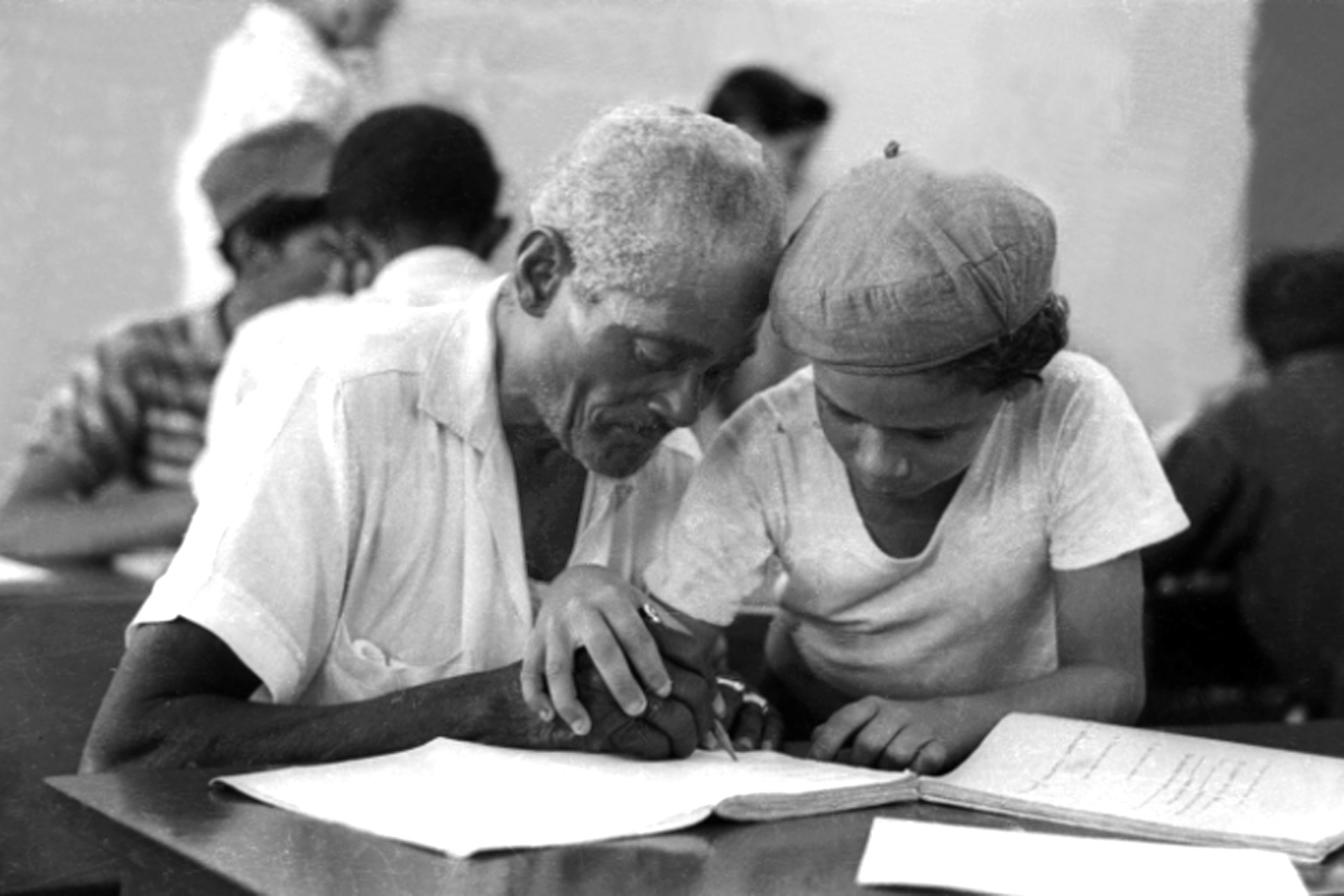 A boy teaches a man to write during a literacy campaign in Cuba in 1961.
