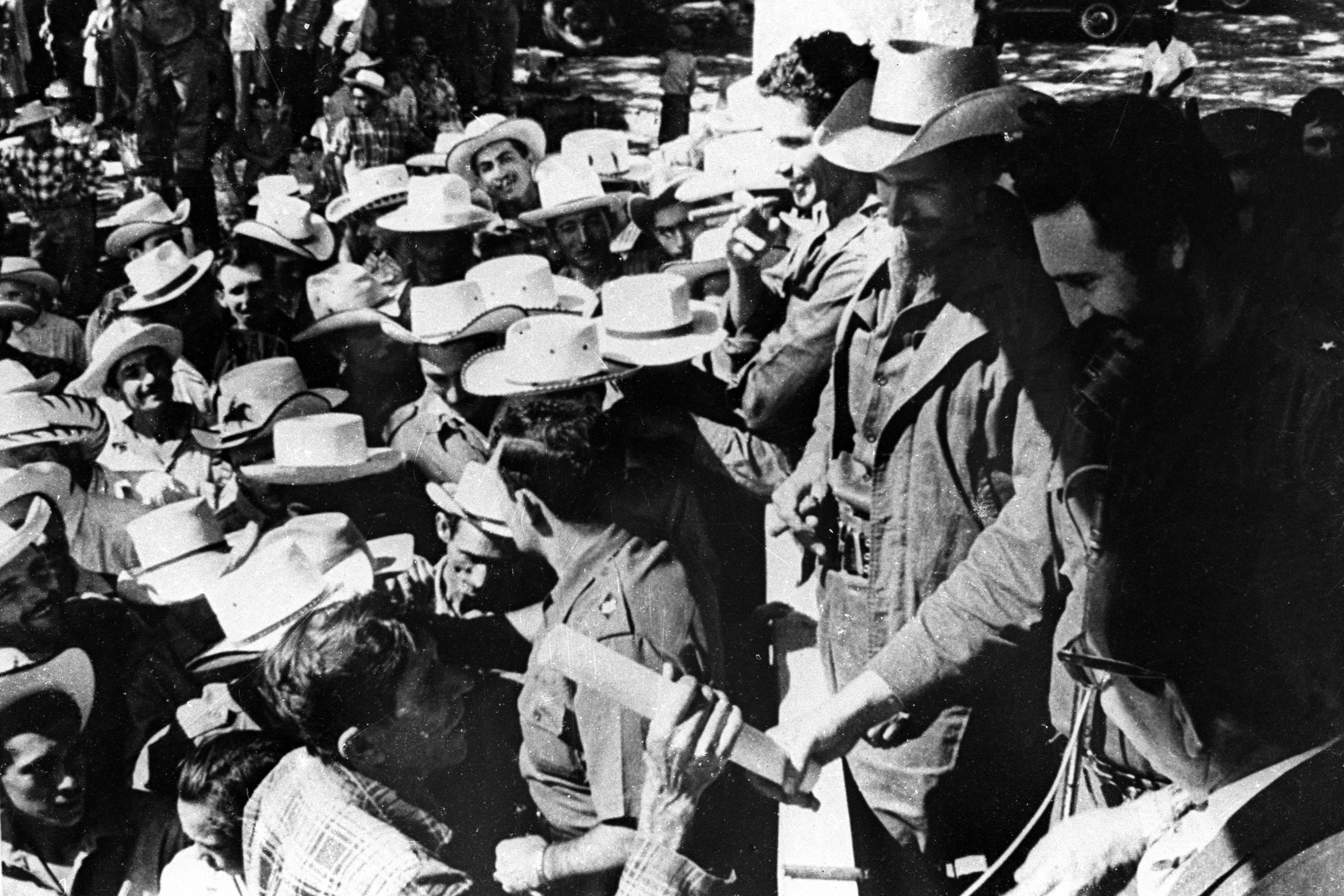 Cuban President Fidel Castro, right, delivers the property title of a land to a peasant following agrarian reform in Cuba in 1960.