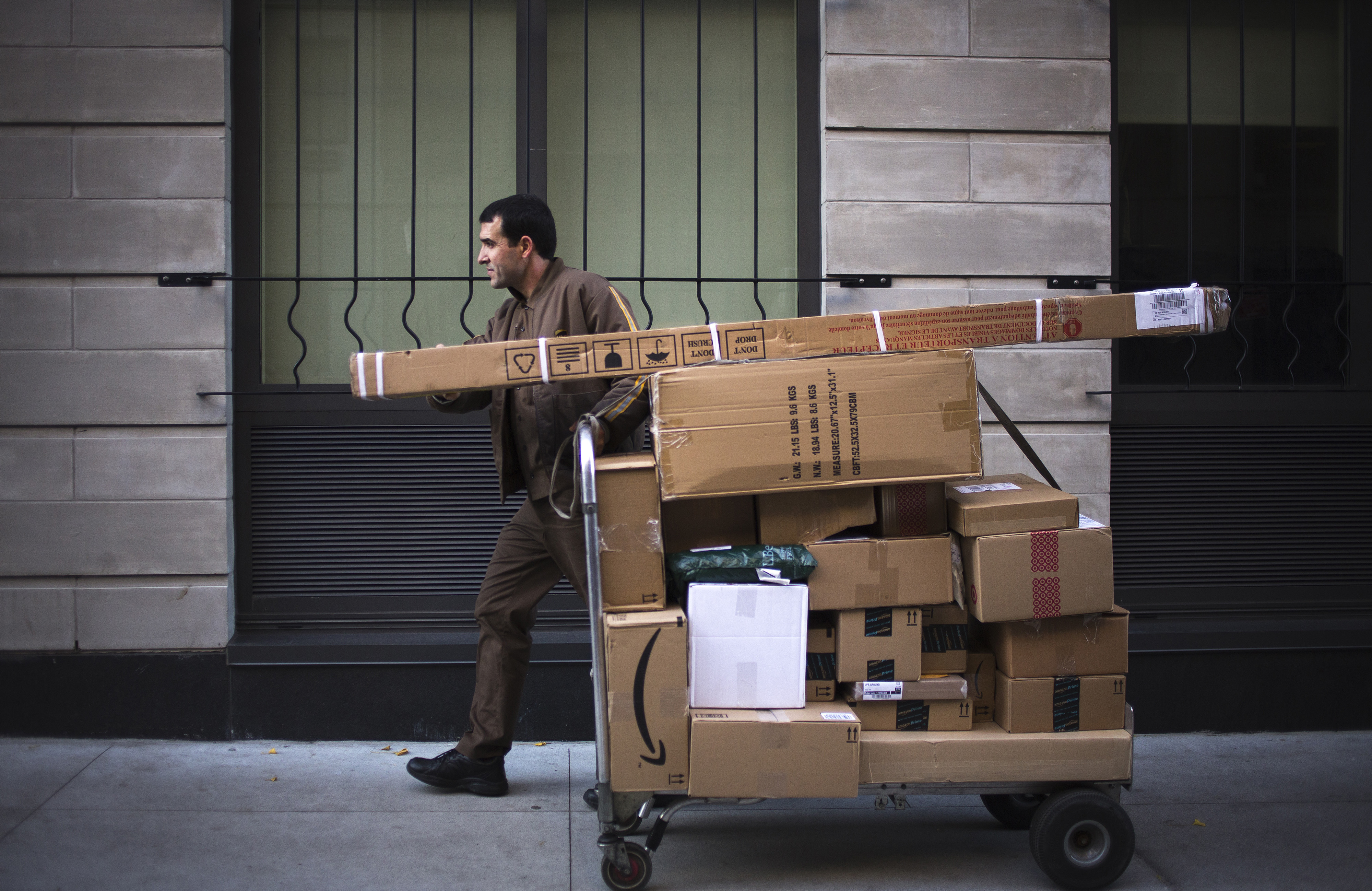 A United Parcel Service Inc. driver pushes a dolly of packages for delivery on Cyber Monday in New York City on Nov. 30, 2015.