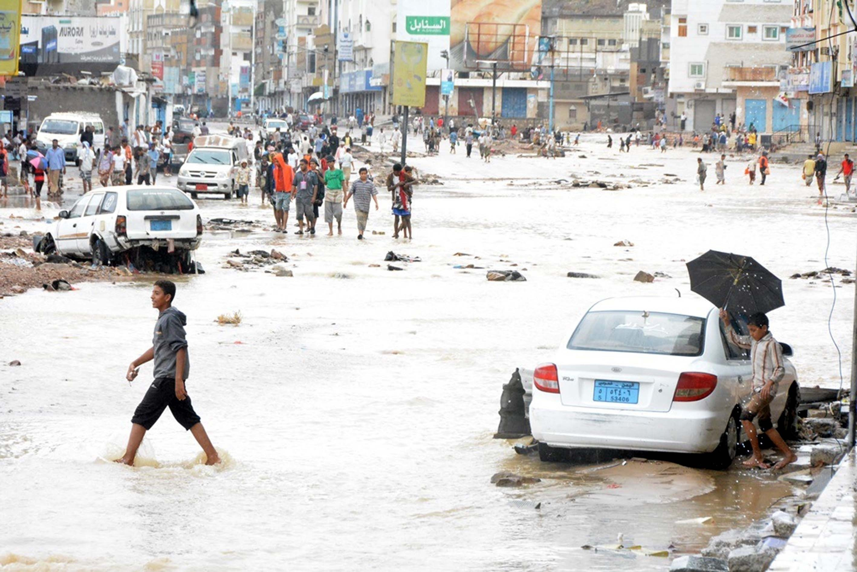 Yemenis walk past the vehicles damaged by wind and heavy rain-caused floodwaters, as a result of Cyclone Chapala on Nov. 03, 2015.