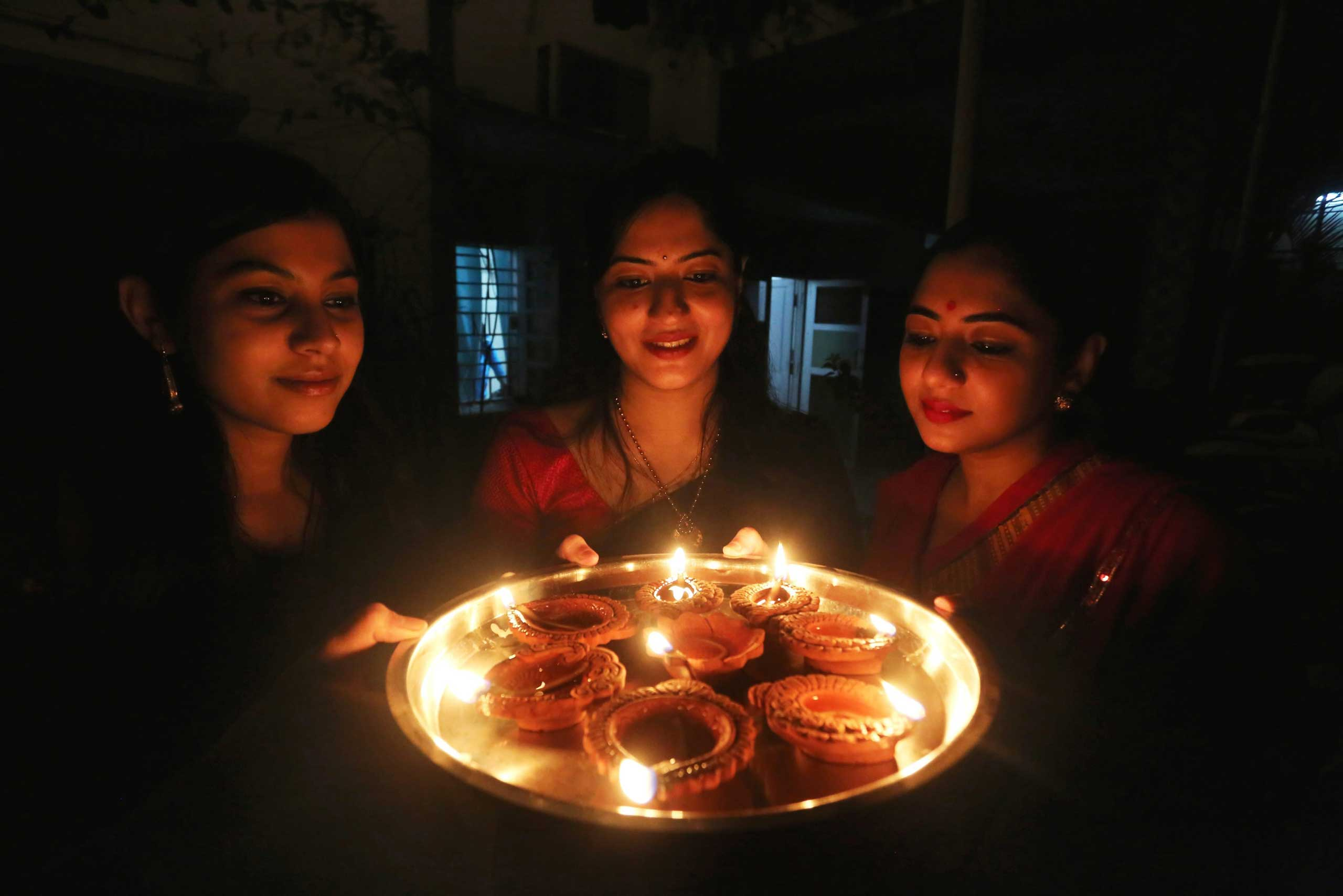 Indian women light lamps on the eve of Diwali festival to mark the event in Bhopal, India, on Nov. 10,  2015.