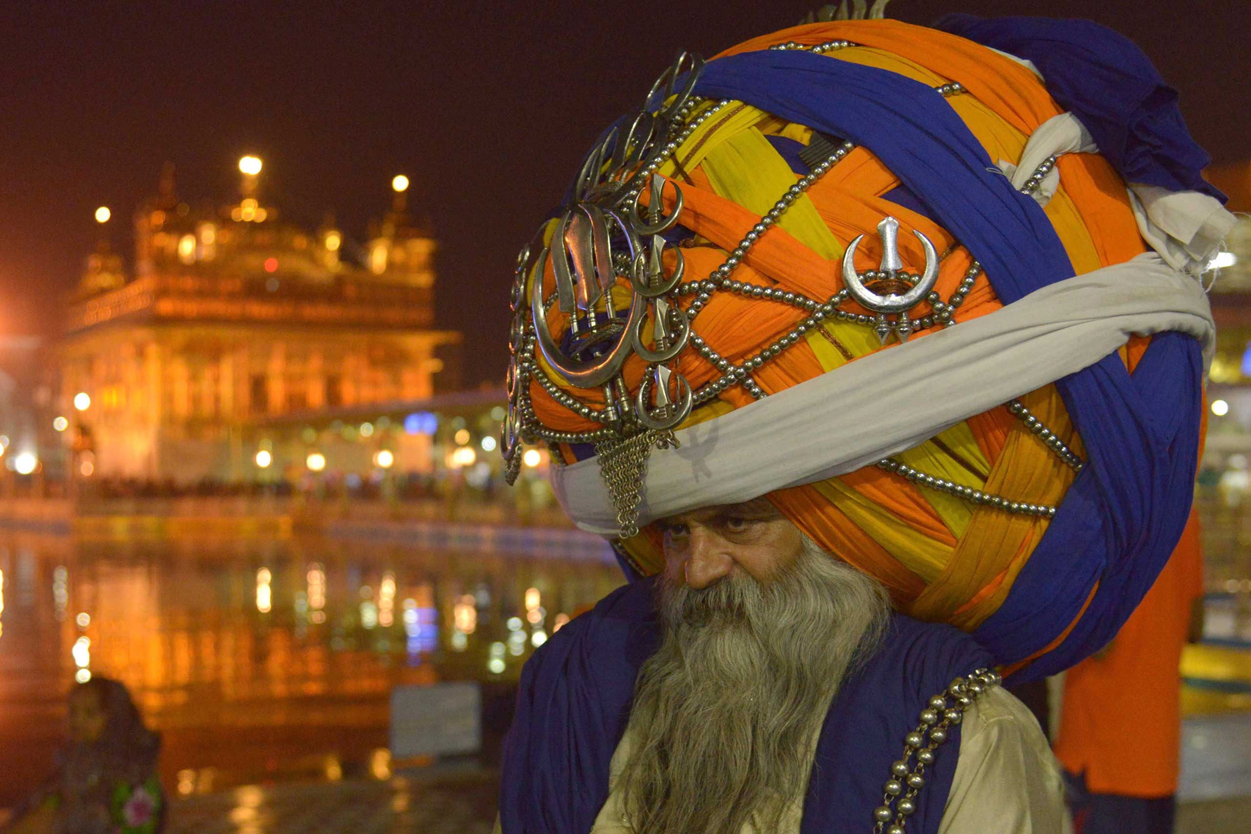 An Indian Sikh Nihang (a traditional Sikh religious warrior) Baba 'Avtar' Singh wears an oversized giant traditional turban as he pay respects at the Golden temple in Amritsar on the eve of Diwali, on Nov. 10, 2015.