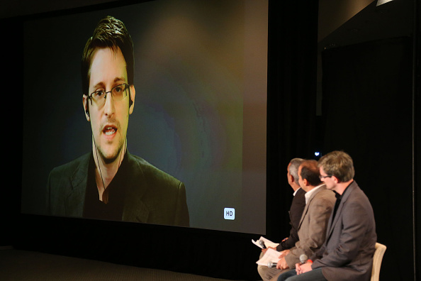 Edward Snowden on monitor speaks to panelist (L-R) Andy Bichlbaum, Mike Bonanno and actor David Neal during Politicon at the Los Angeles Convention Center on October 10, 2015 in Los Angeles, California.