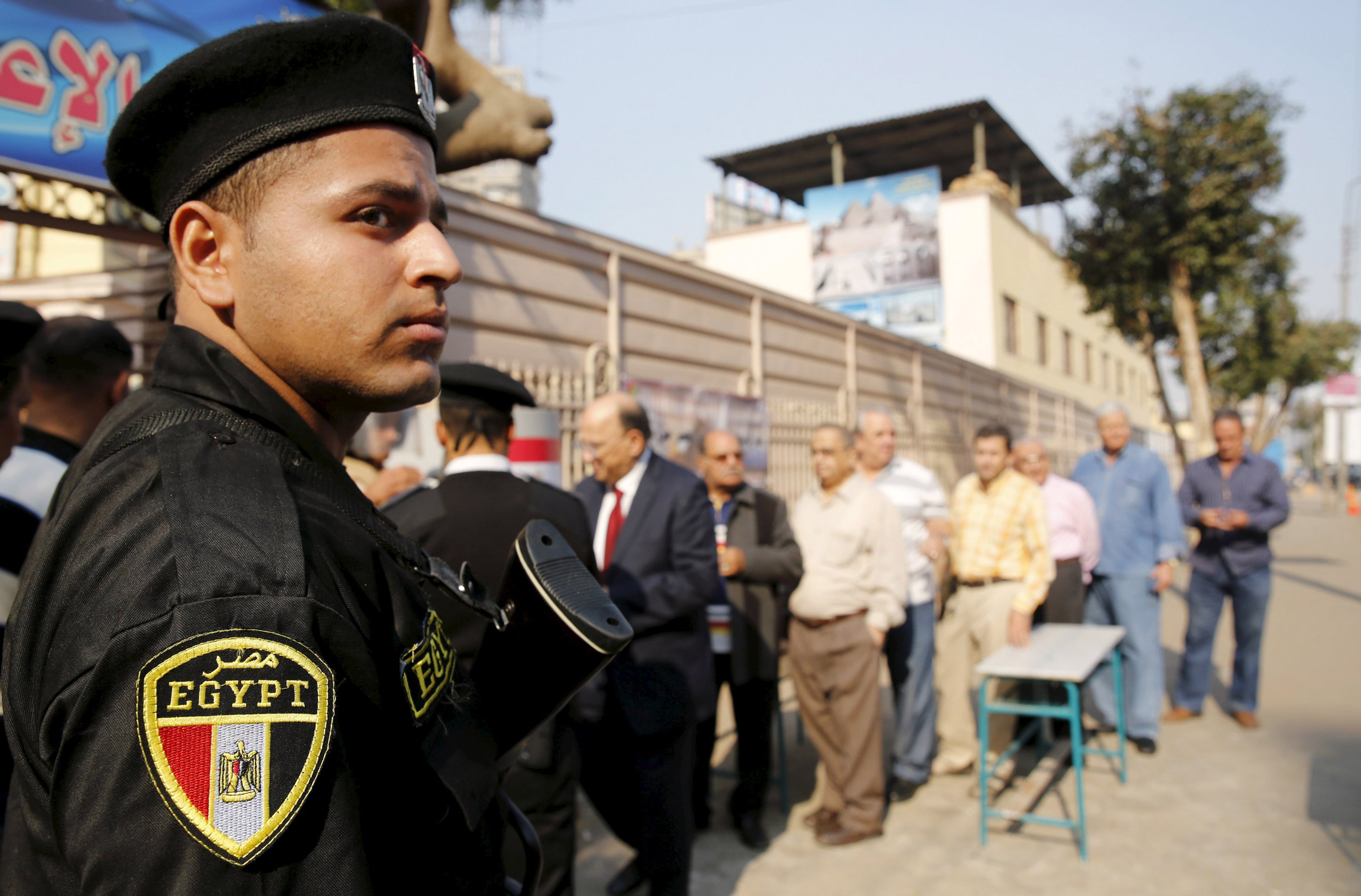 A policeman stands guard in front of people lining up to vote at school used as a polling station during the second round of parliament elections at Heliopolis in Cairo on Nov. 22, 2015.