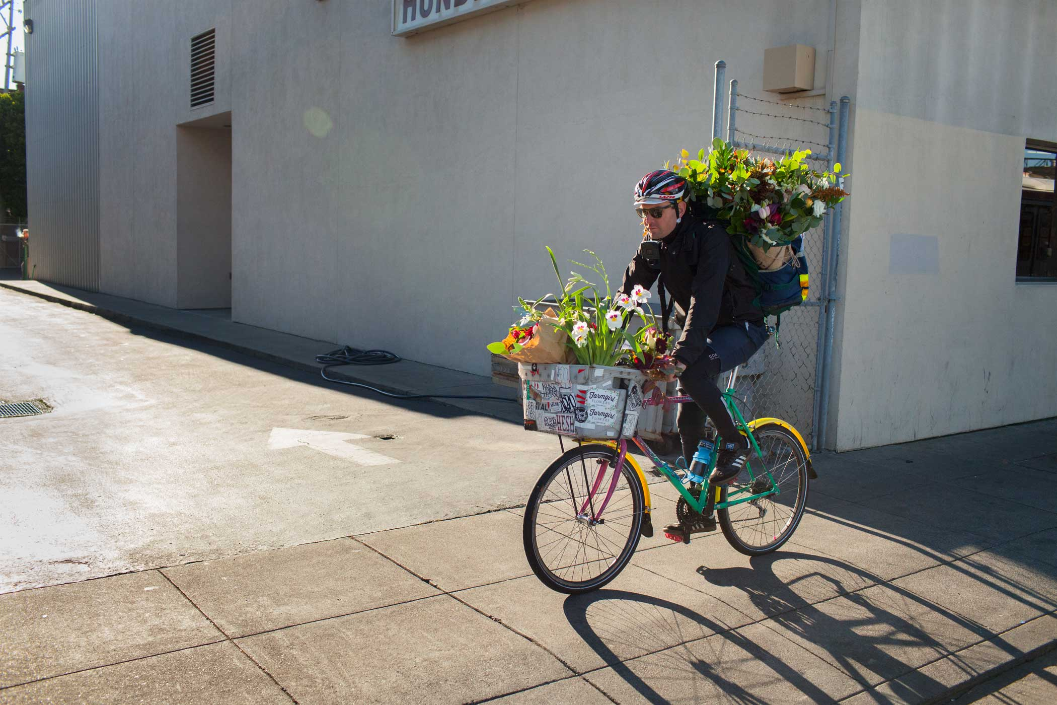 A flower delivery employee bikes to deliver his first flowers of the day.