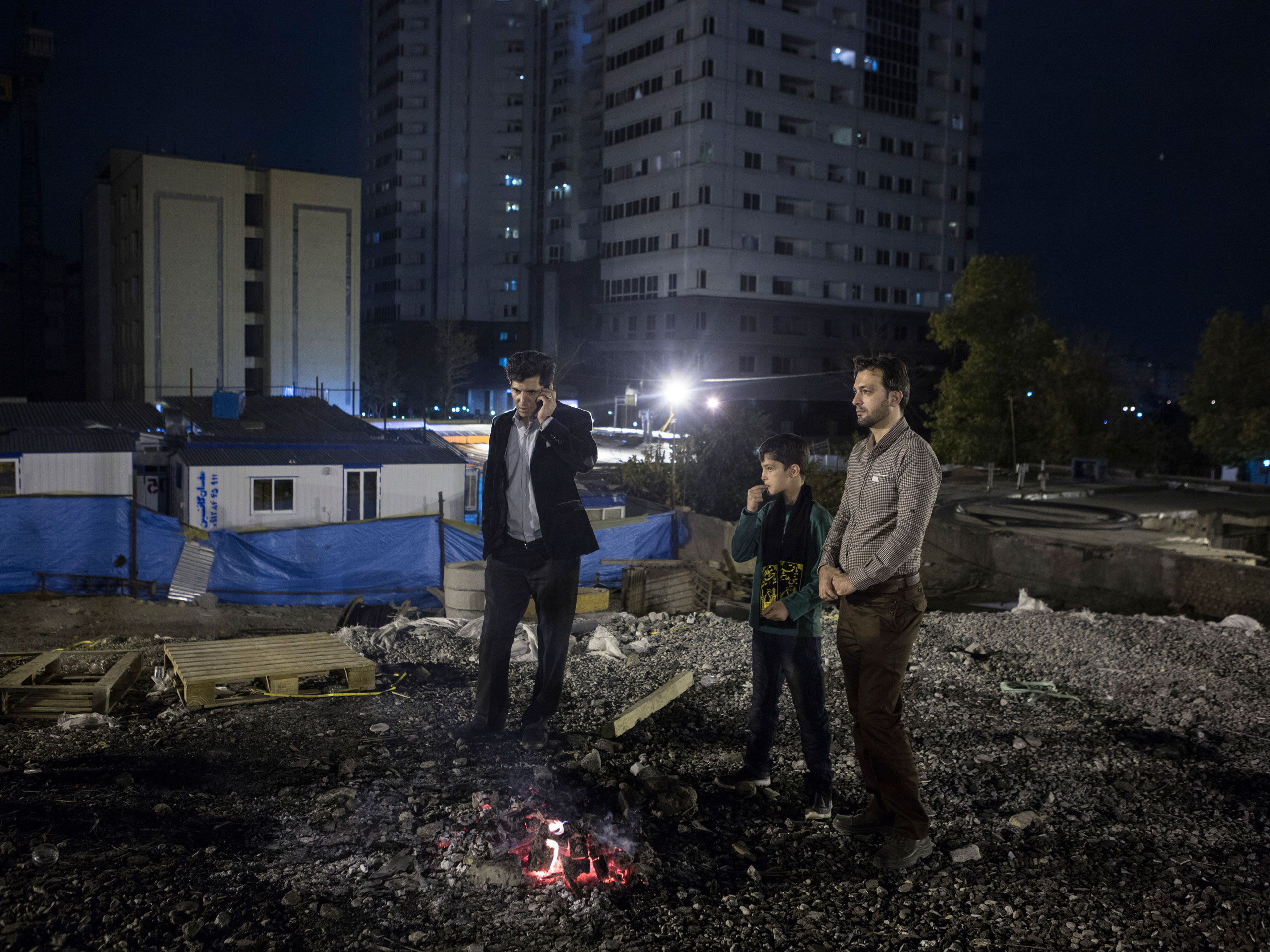 Two men and a boy stand next to a fire at a construction site in Tehran, where there is a rise in new construction.
