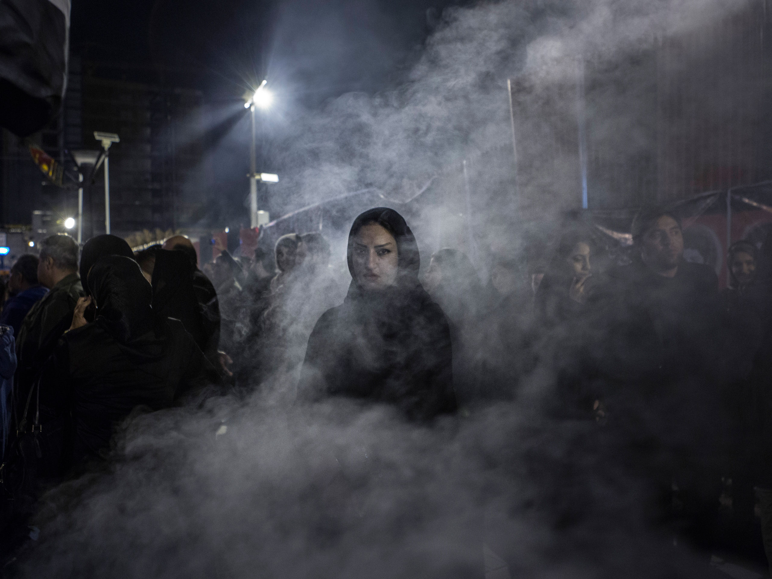 An Iranian woman walks through a haze of smoke caused by the burning of the herb esfand. According to popular belief, this ritual drives away the evil eye.