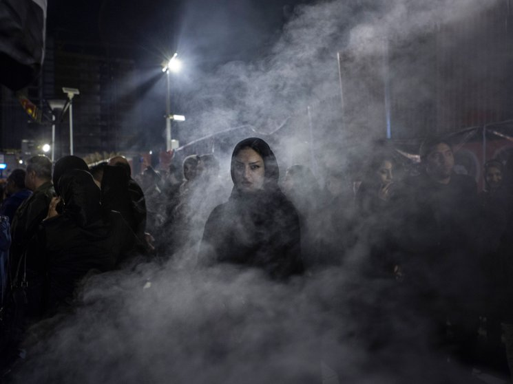 An Iranian women walks through a haze of smoke caused by the burning of 'esfand', a herb. According to popular belief this drives away the evil eye.