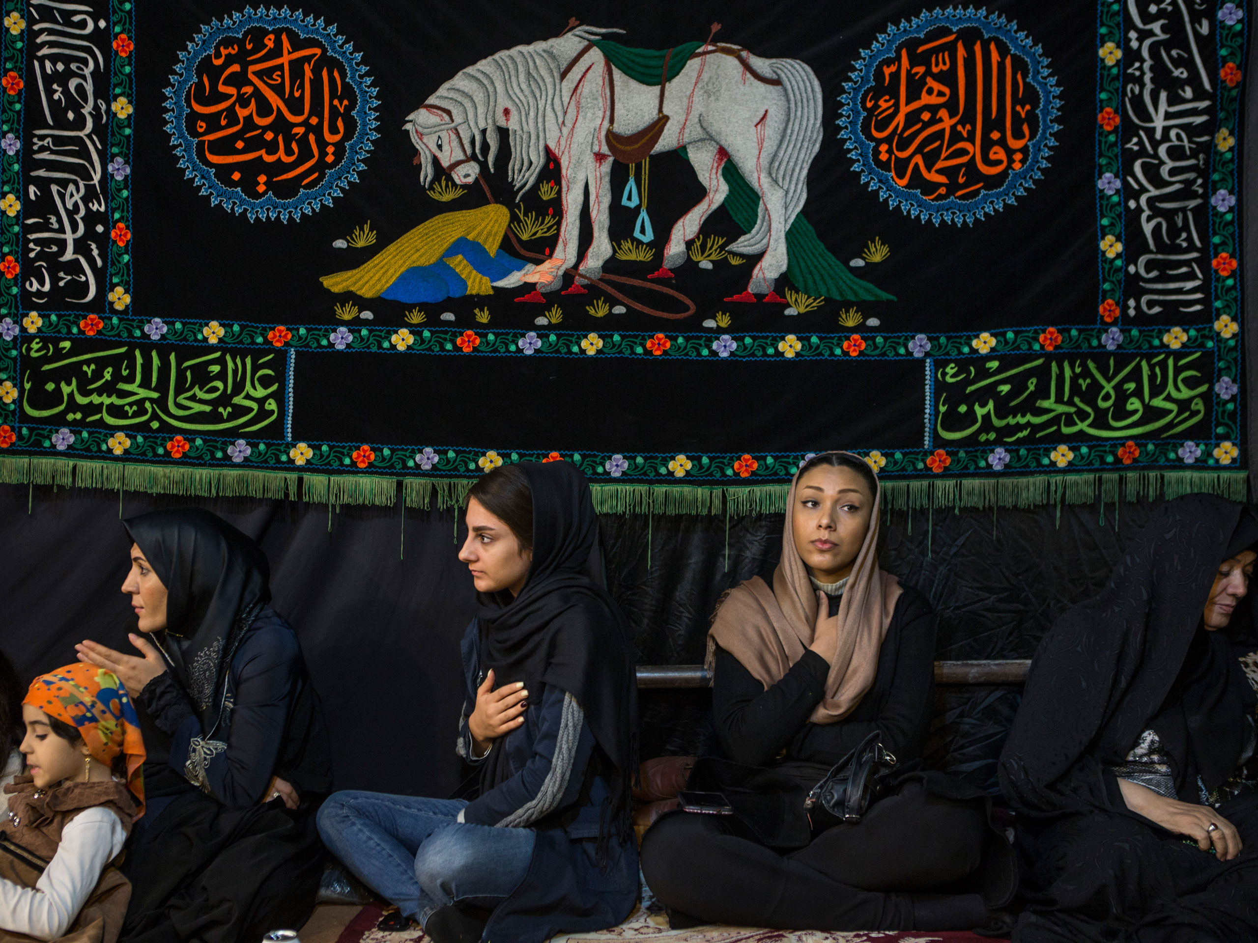 Iranian women beat their chests as they listen to a female religious chanter, in a makeshift tent in western Tehran.