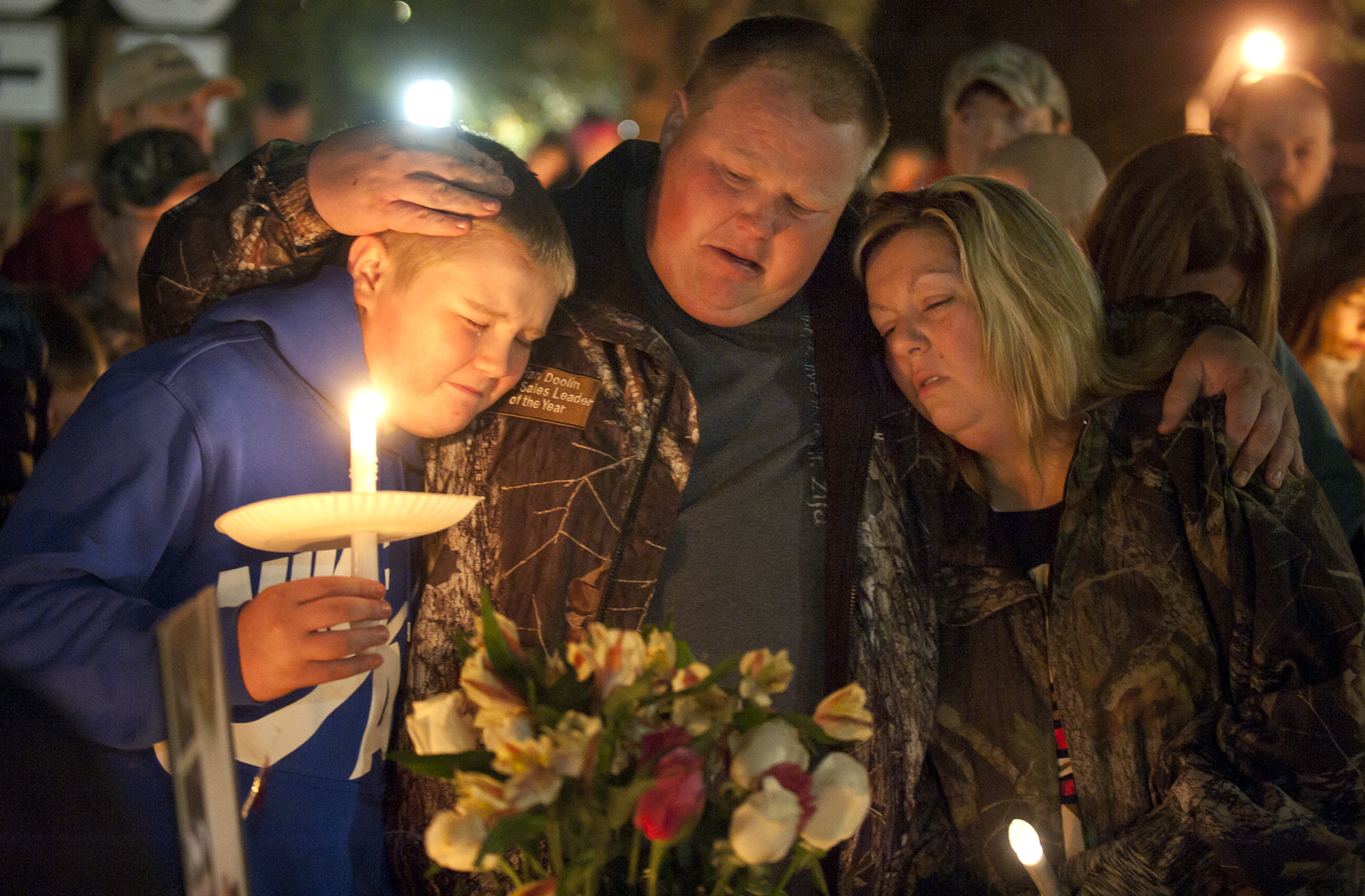 Gabriella Doolin's brother Alec, father Brian and mother Amy, comfort each other during a vigil for her in Scottsville, Kentucky on Nov. 15, 2015.