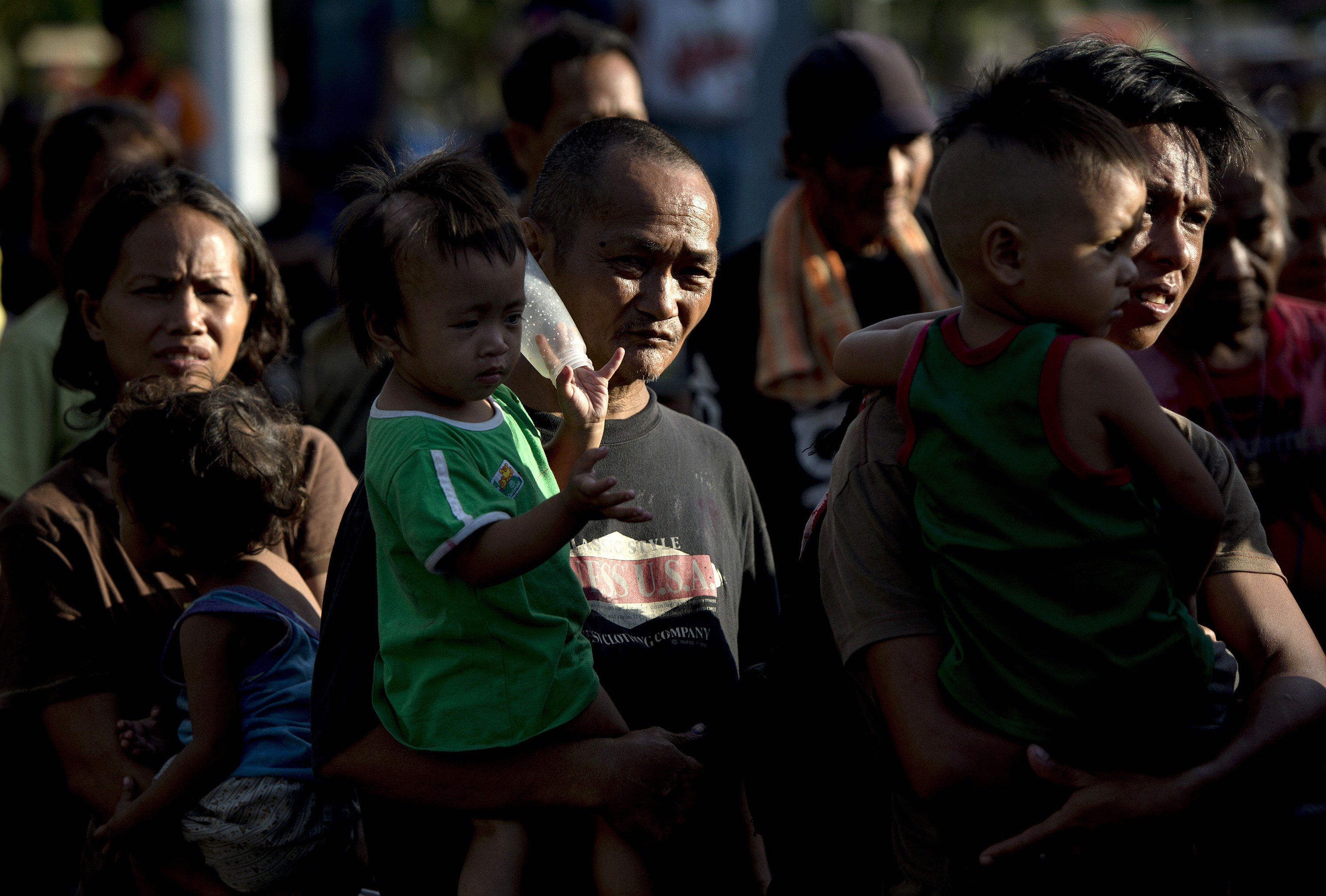 Homeless people queue to recieve food and clothing from a charity group at a park in Manila on August 24, 2014. read NOEL CELIS/AFP/Getty Images)