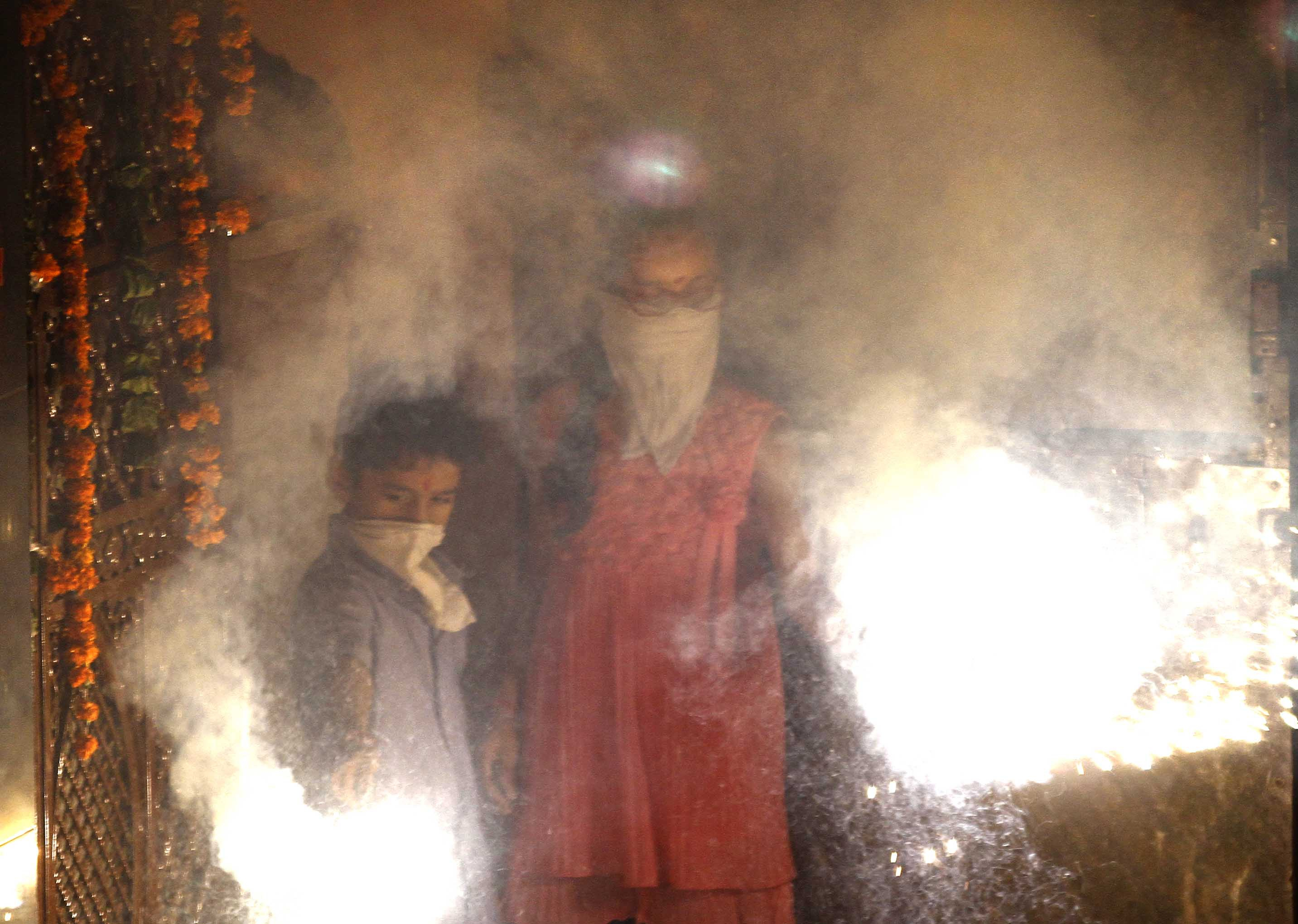 People bursting firecrackers as they celebrate Diwali, the Festival of Light, on Oct. 23, 2014, in New Delhi