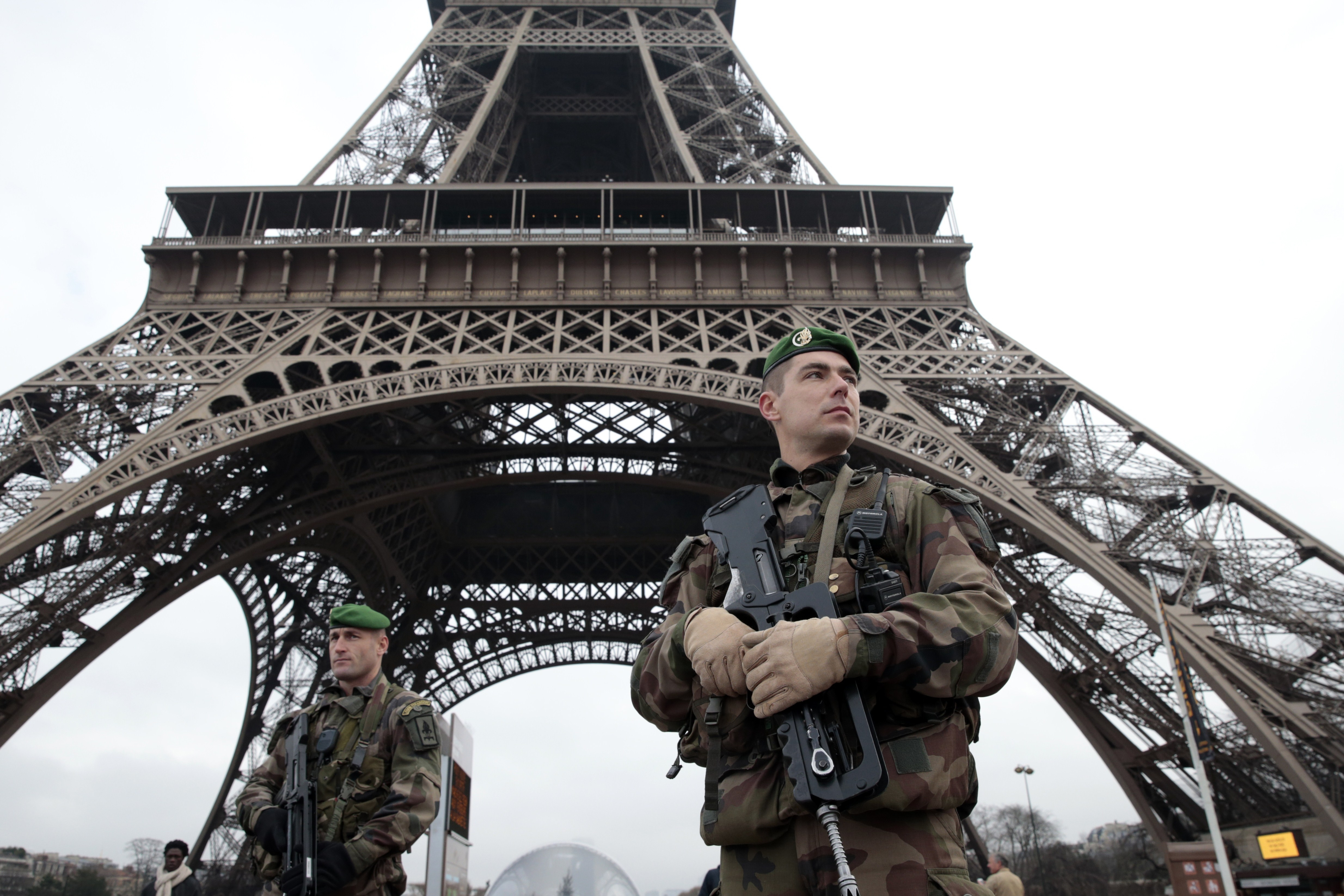 French soldiers patrol in front of the Eiffel Tower on January 7, 2015 in Paris as the capital was placed under the highest alert status after heavily armed gunmen shouting Islamist slogans stormed French satirical newspaper Charlie Hebdo and shot dead at least 12 people in the deadliest attack in France in four decades.