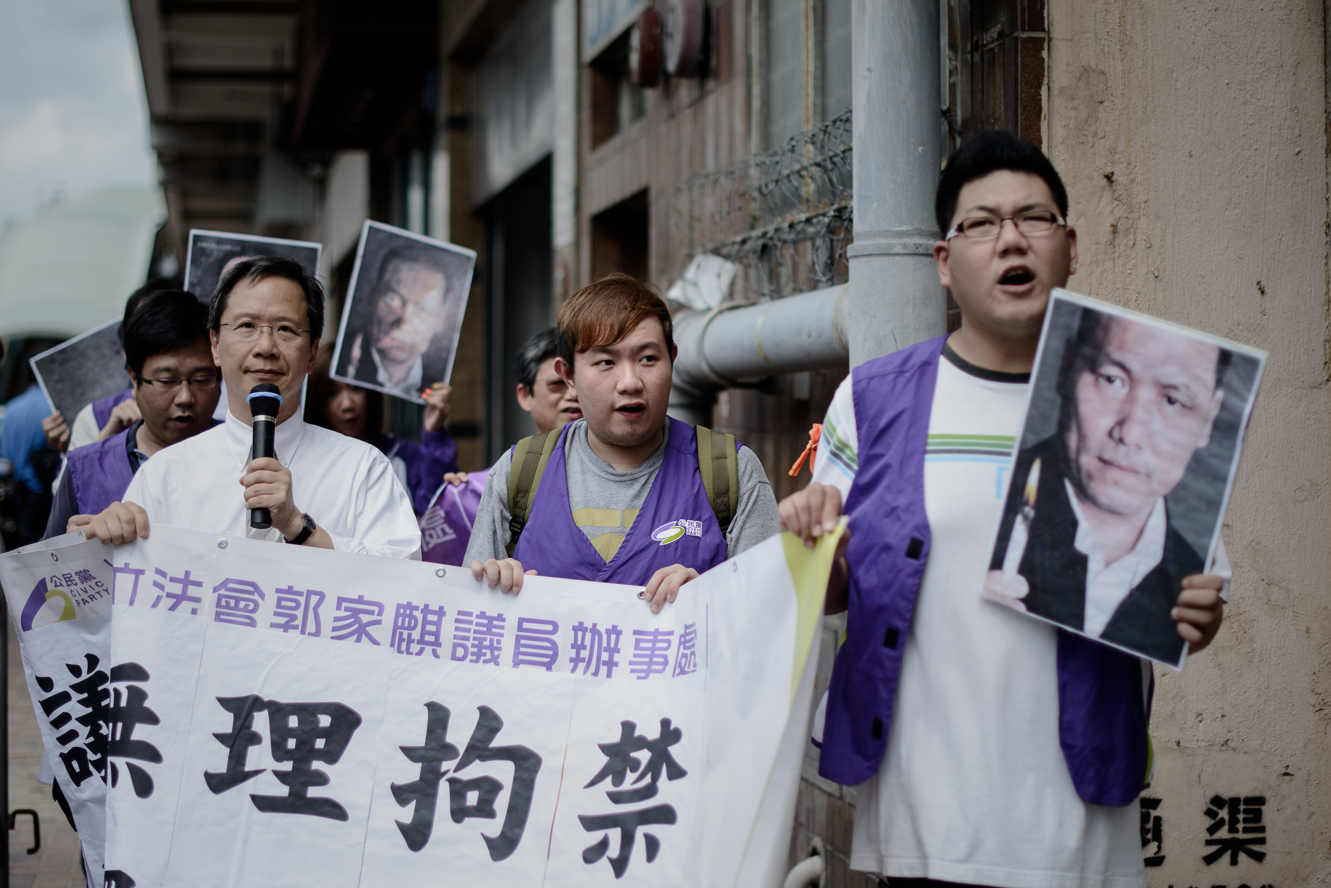 Protesters holding pictures of detained Chinese human-rights lawyer Pu Zhiqiang march to the Chinese Liaison Office in Hong Kong on May 14, 2014, asking for his release