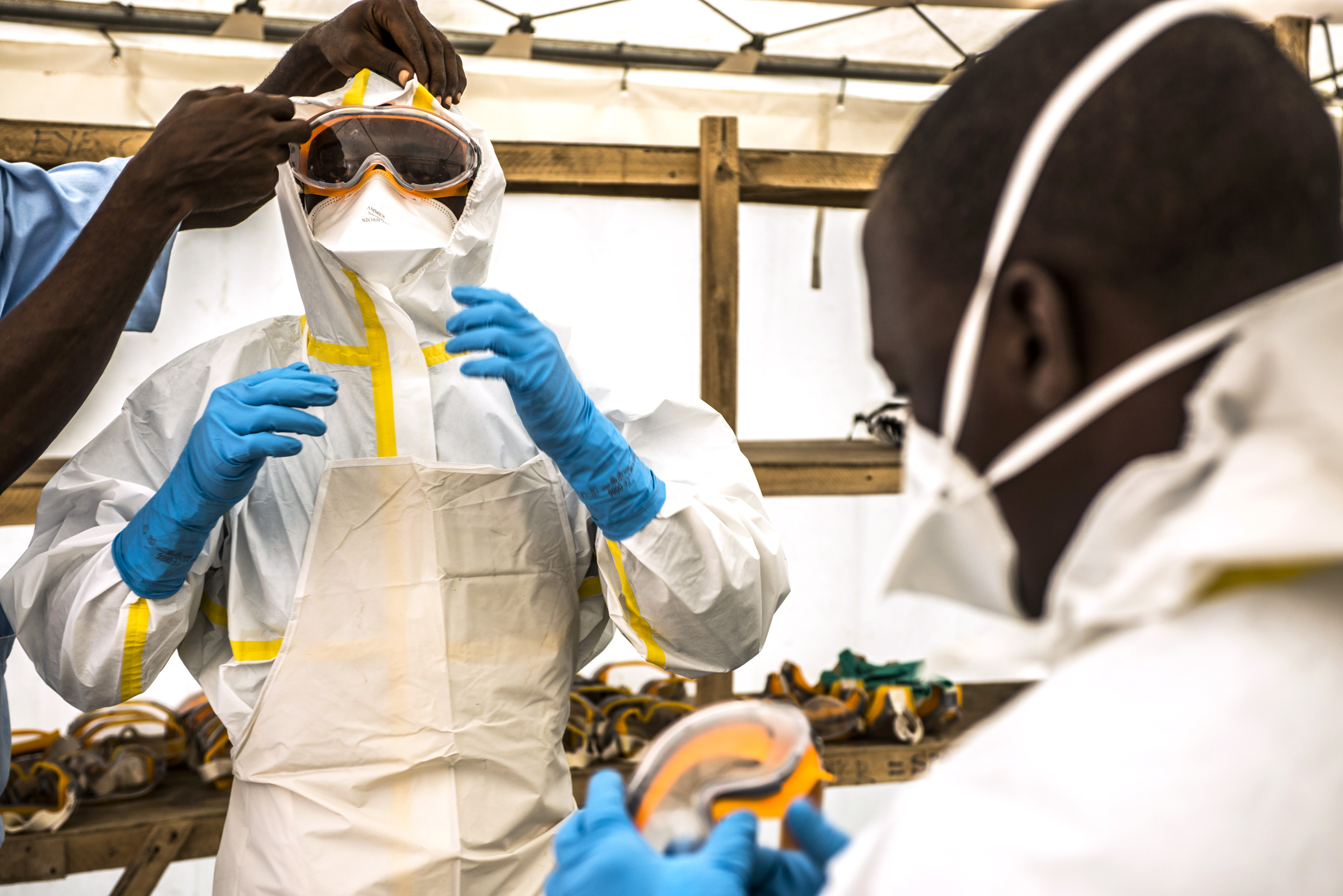 A healthcare worker helps a colleague dress in protective gear at an Ebola treatment center in Guinea, Sept. 10, 2015